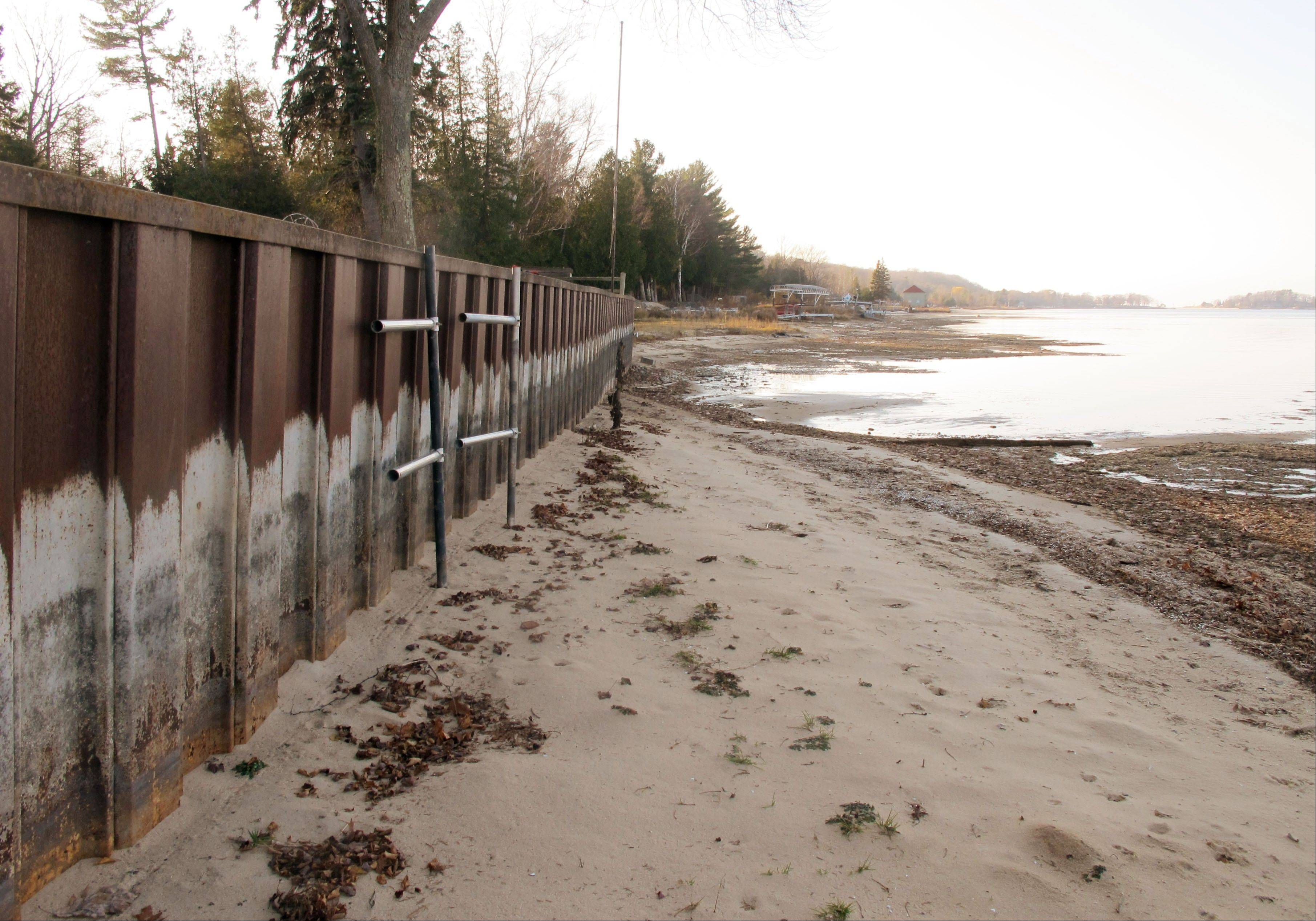 The white streaks on a steel breakwall show the normal water level on Portage Lake at Onekama, Mich., which is connected by a channel to Lake Michigan. Levels across much of the Great Lakes are abnormally low, causing problems for small harbor towns that rely on boating and water tourism.