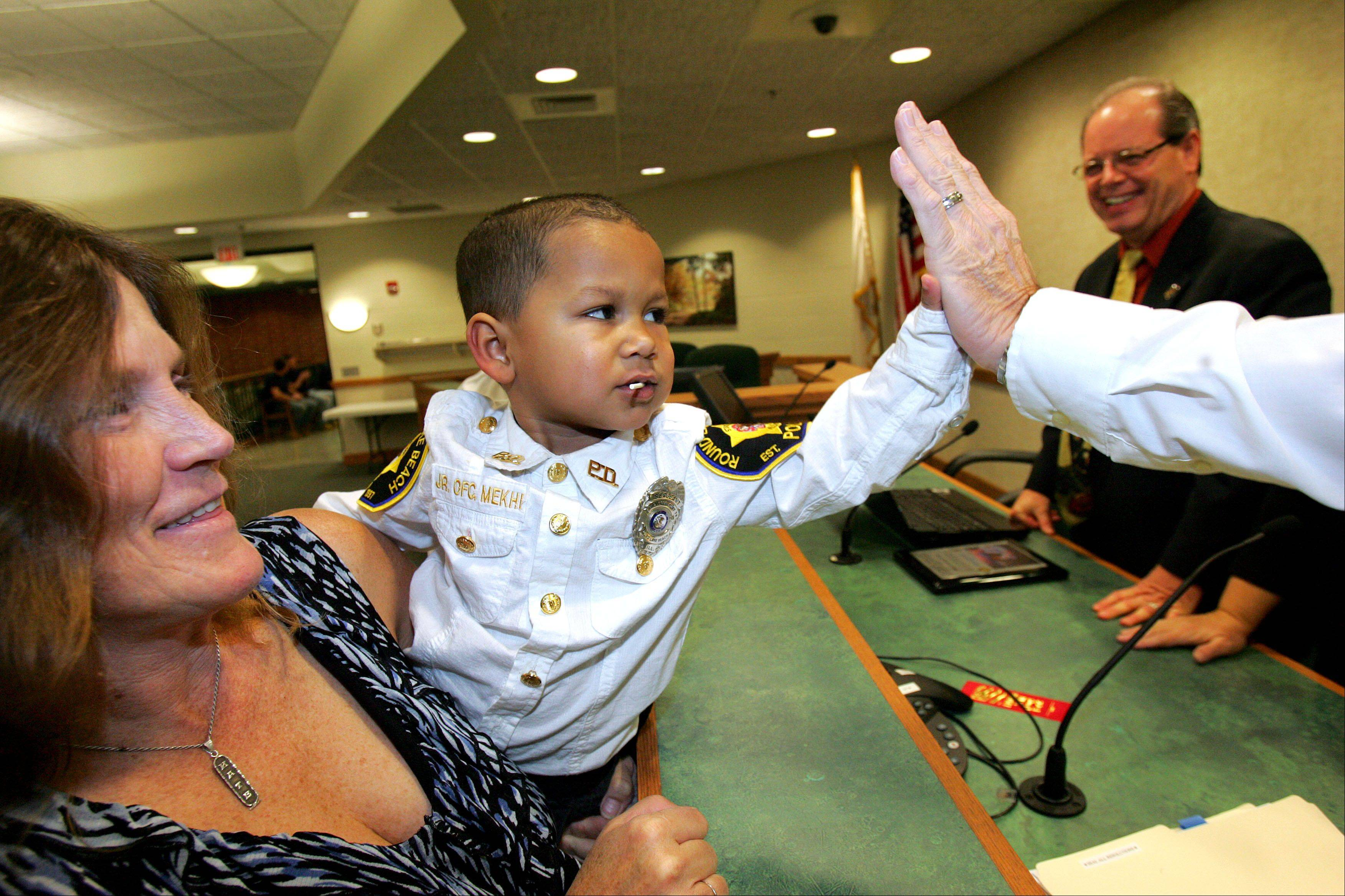 Mekhi Carter is held by his grandmother, Katie Hoftender, as he high-fives members of the Round Lake Beach village board. The 3�-year-old Antioch Township boy was recognized by village officials as a Junior Round Lake Beach Police Officer as a wish enhancement in conjunction with the Make-A-Wish foundation.