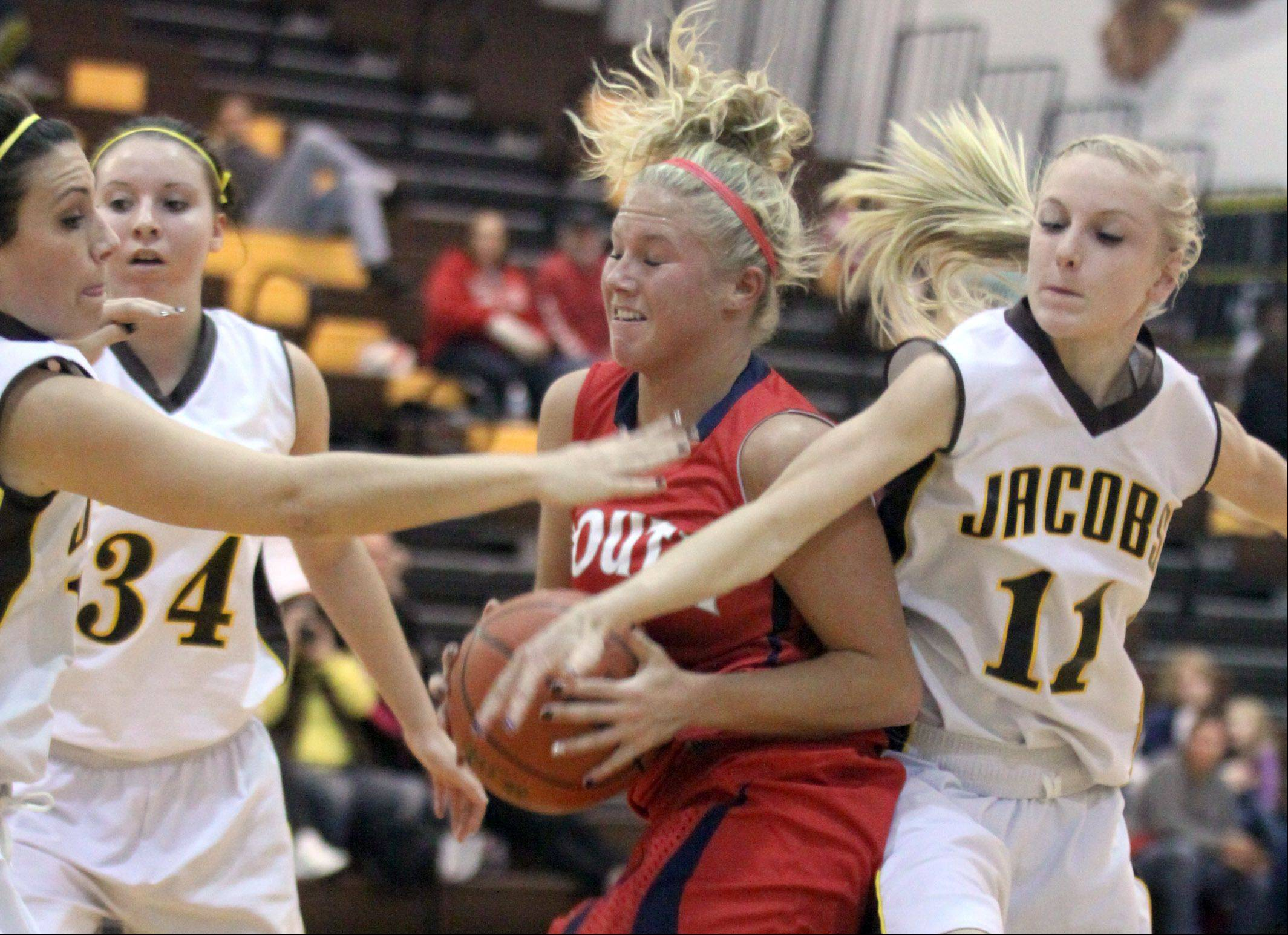 Jacobs� Payton Berg, left, and Lauren Van Vlierbergen, right try to stop the progress of South Elgin�s Kara Rodriguez, center, during a varsity basketball game at Algonquin on Tuesday night.