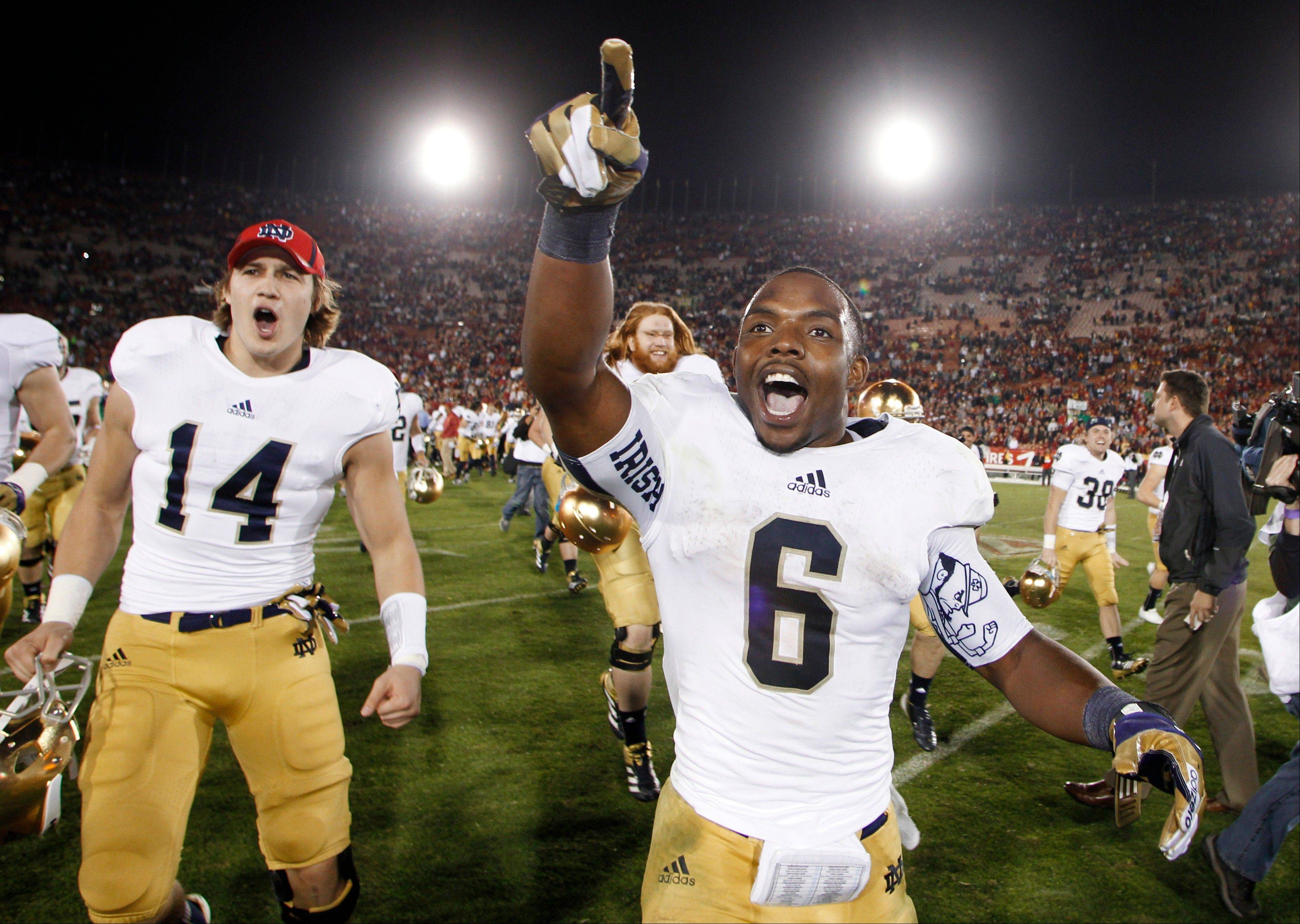 Notre Dame was unranked at the start of the college football season in The AP Top 25 poll, but the Fighting Irish, as running back Theo Riddick, right, and wide receiver Luke Massa point out, finished the regular season ranked No. 1.