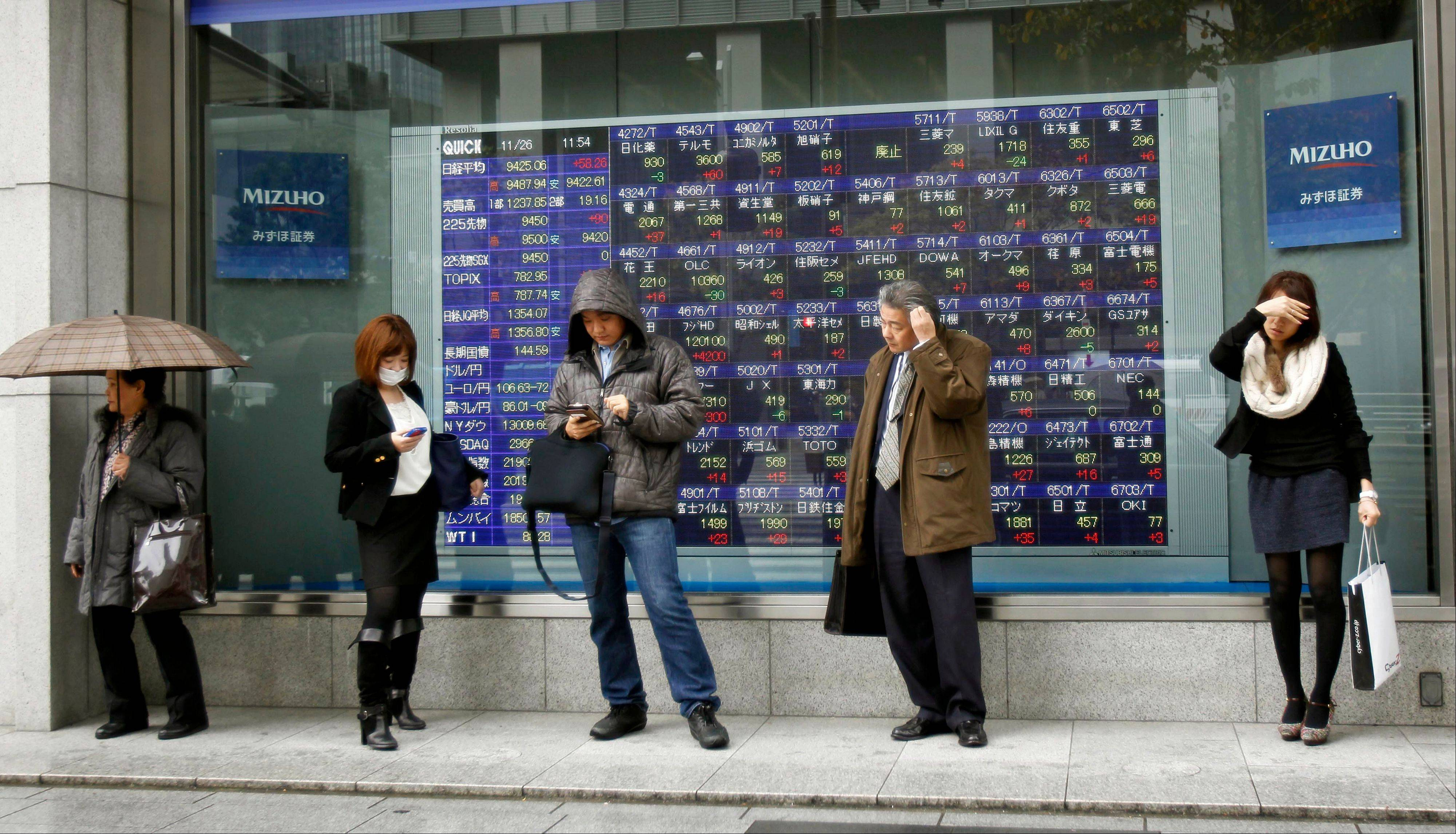 People stand in the rain in front of the electronic stock board of a securities firm in Tokyo, Monday.
