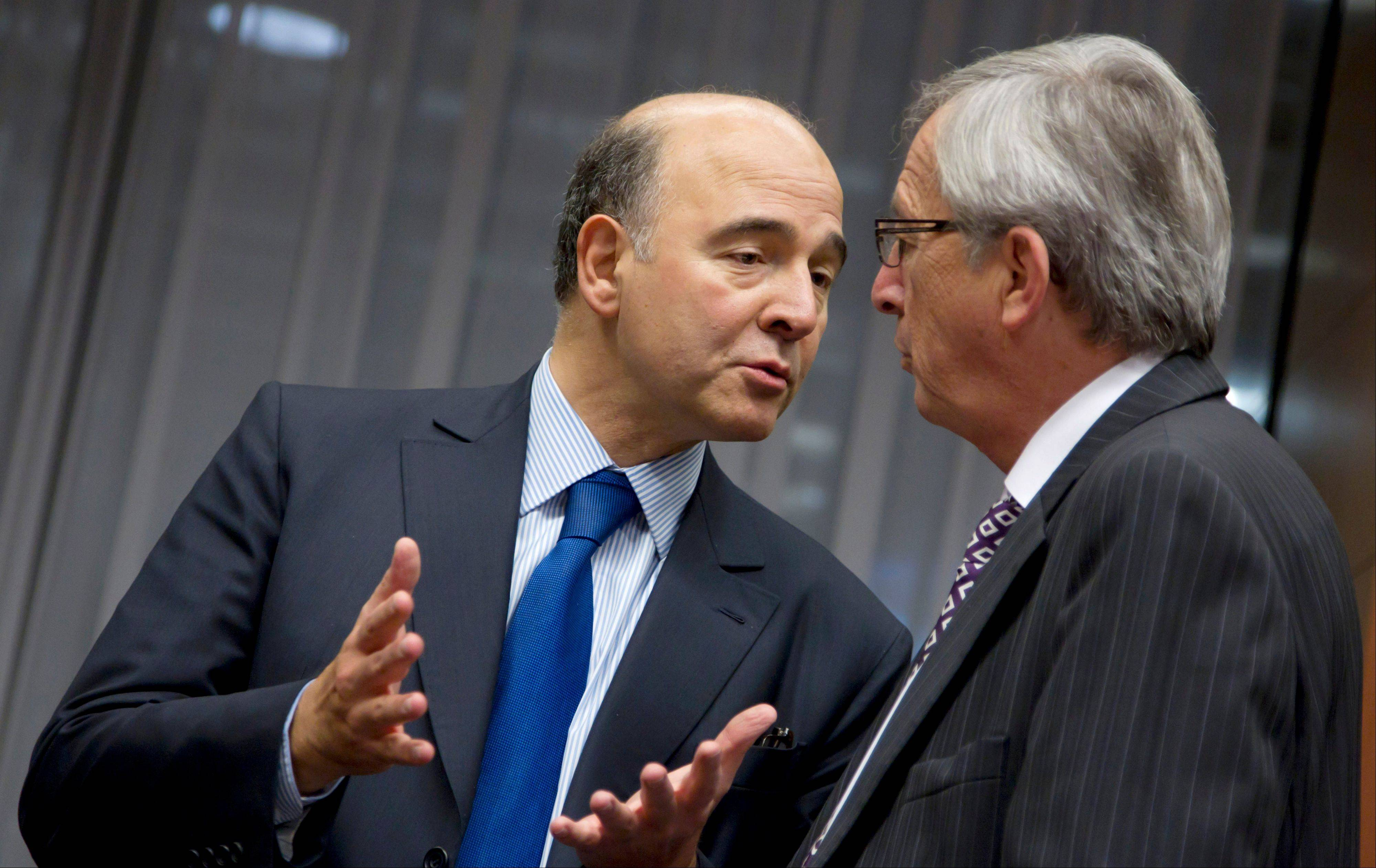 Luxembourg's Prime Minister Jean-Claude Juncker, right, speaks with French Finance Minister Pierre Moscovici during a meeting of eurogroup finance ministers in Brussels.