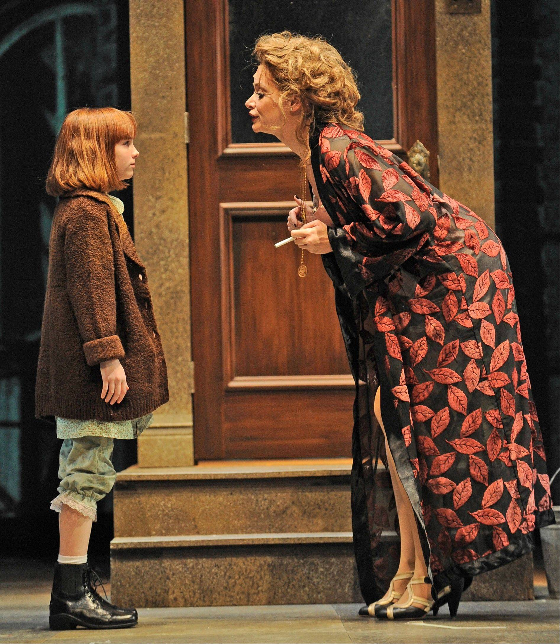 "Annie (Caroline Heffernan) is confronted by Miss Hannigan (Christine Sherrill) in a holiday production of the 1977 Broadway musical ""Annie"" at the Paramount Theatre in Aurora."