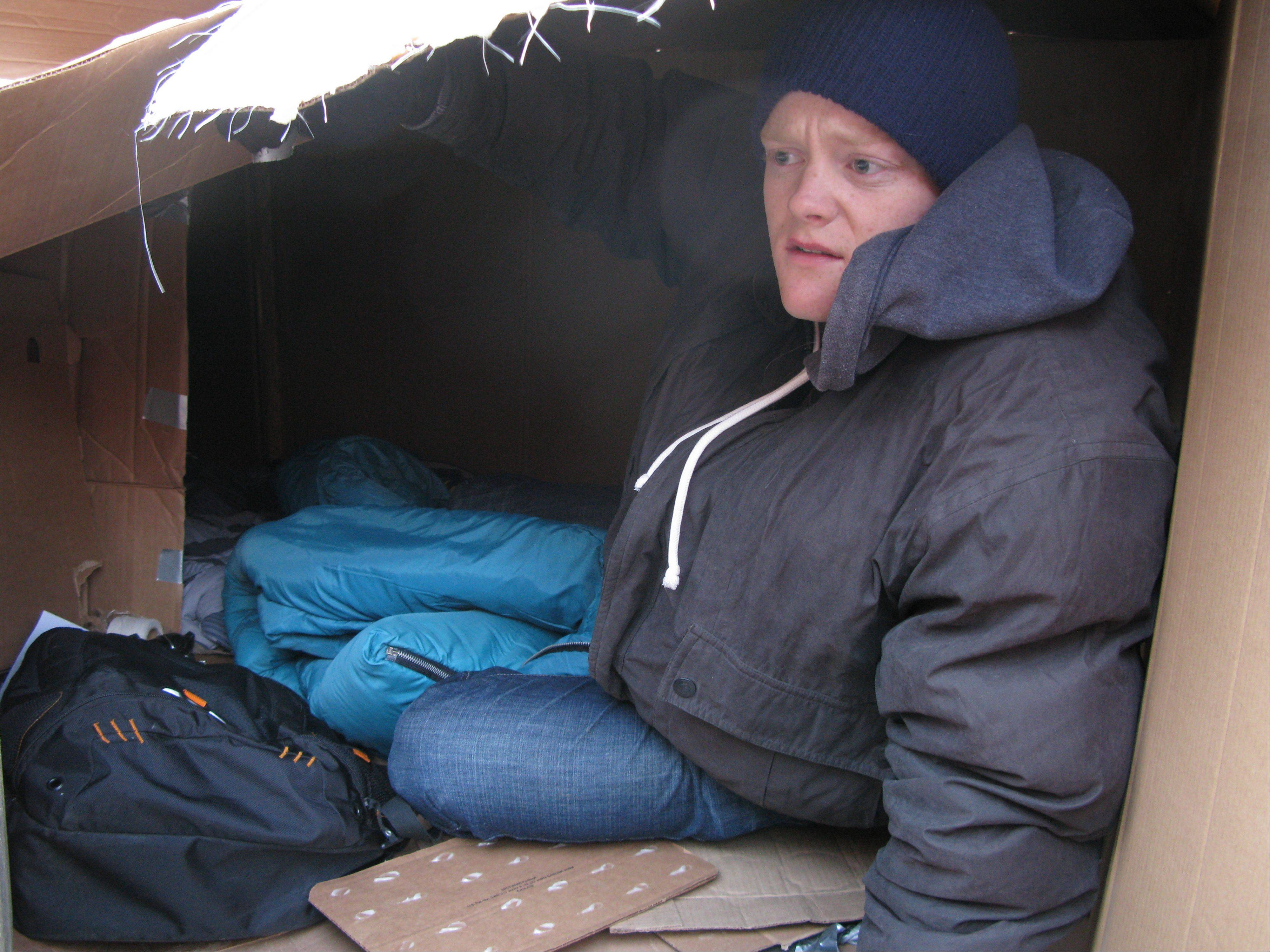 Oakton Community College student Ryan Alm describes how he kept warm while sleeping outdoors in a cardboard box to experience firsthand what it would be like to be homeless. Roughly 27 students stayed through the night in shanties they built out of discarded cardboard boxes in the courtyard of the Des Plaines campus.