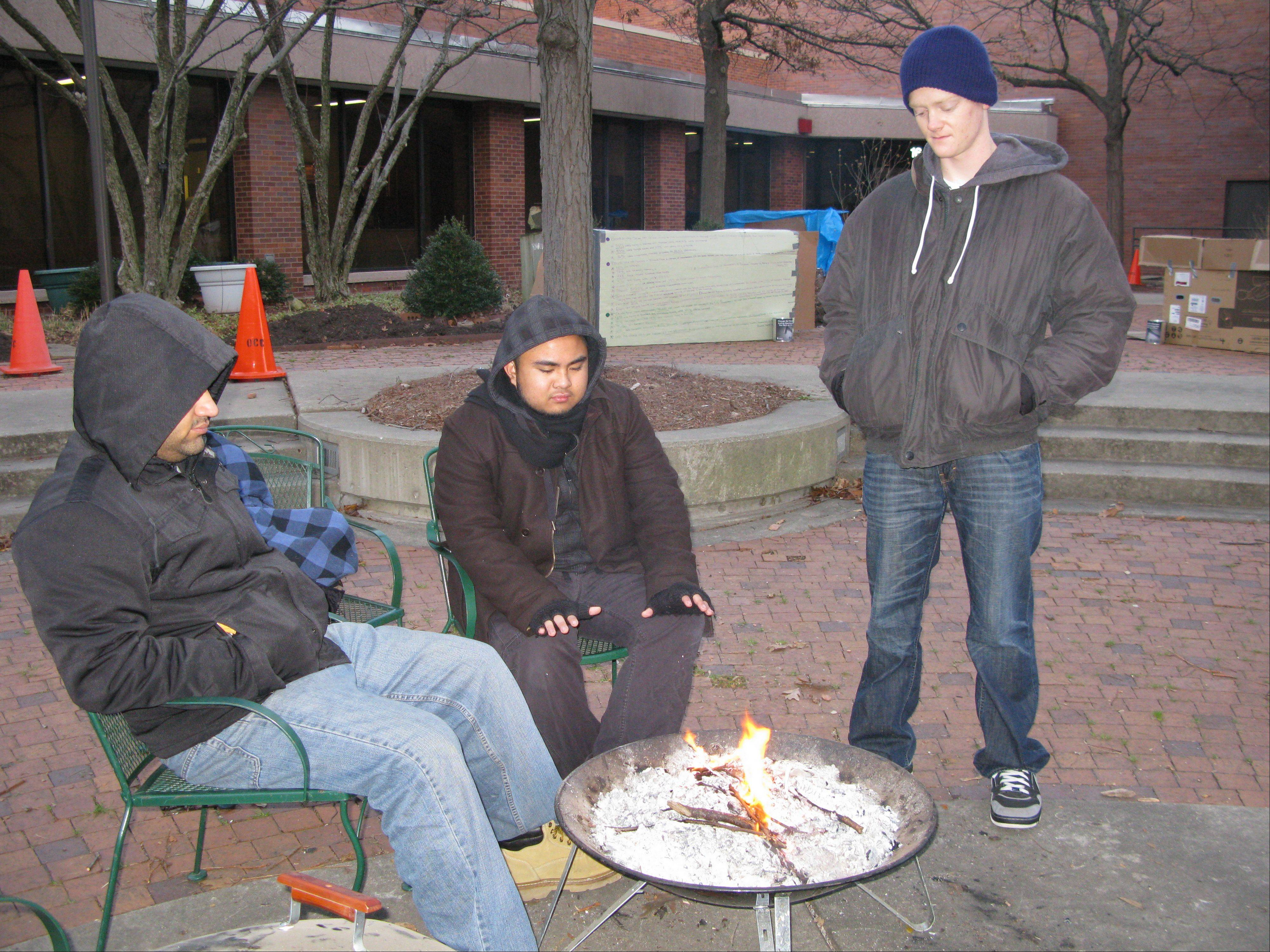 From left, Oakton Community College students Sahil Pruthi, Jonathan Narcise and Ryan Alm huddle around a fire Wednesday morning to keep warm after spending a night out in the cold to experience firsthand what it would be like to be homeless. Roughly 27 students stayed through the night in shanties they built out of discarded cardboard boxes in the courtyard of the Des Plaines campus.