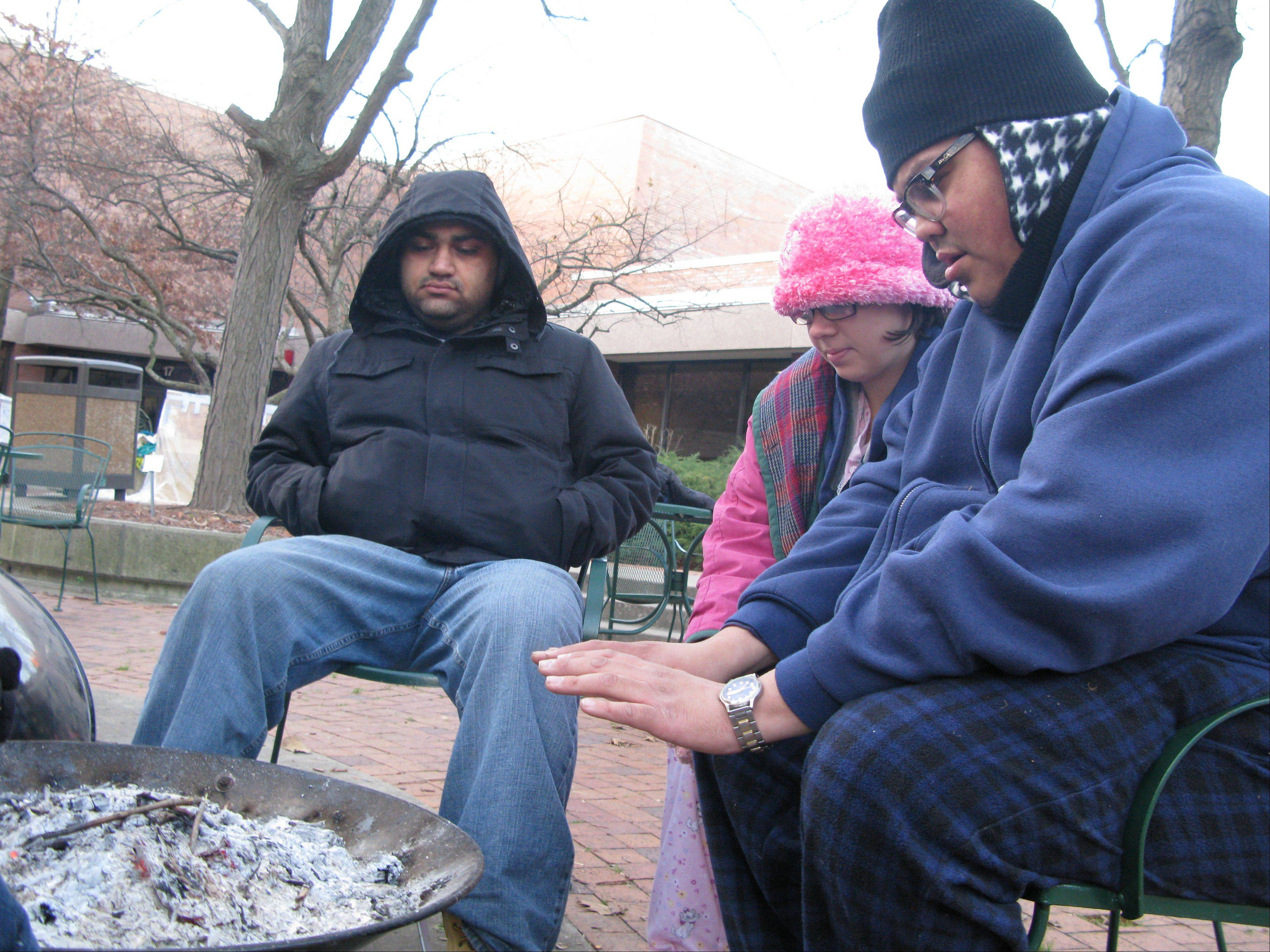From left, Oakton Community College students Sahil Pruthi, Elizabeth Adcox and Ben Miller huddle around a fire Wednesday morning to keep warm after spending a night out in the cold to experience firsthand what it would be like to be homeless. Roughly 27 students stayed through the night in shanties they built out of discarded cardboard boxes in the courtyard of the Des Plaines campus.