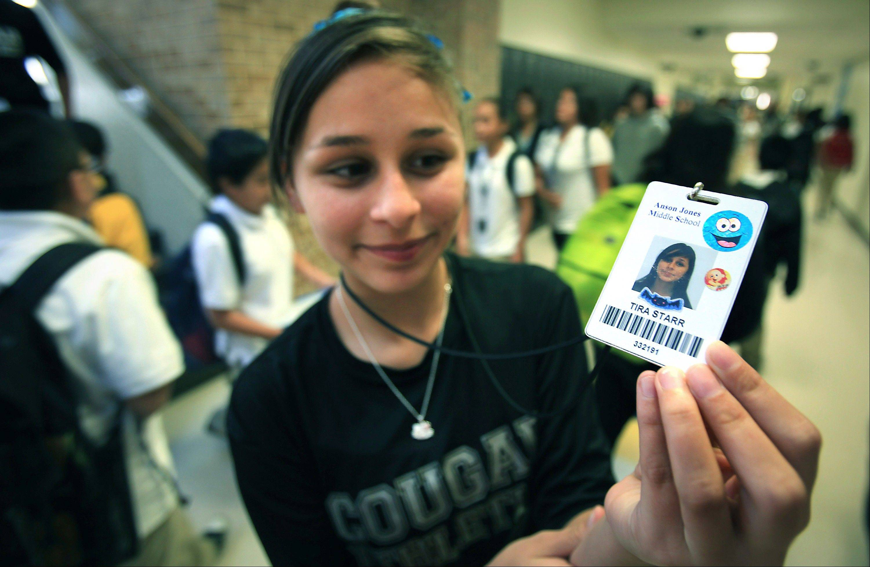 Tira Starr, an 8th grader at Anson Jones Middle School, shows her ID badge as students change classes in San Antonio, Texas. All students at the school are required to carry identification cards embedded with a microchip. They are tracked by the dozens of electronic readers installed in the schools' ceiling panels.