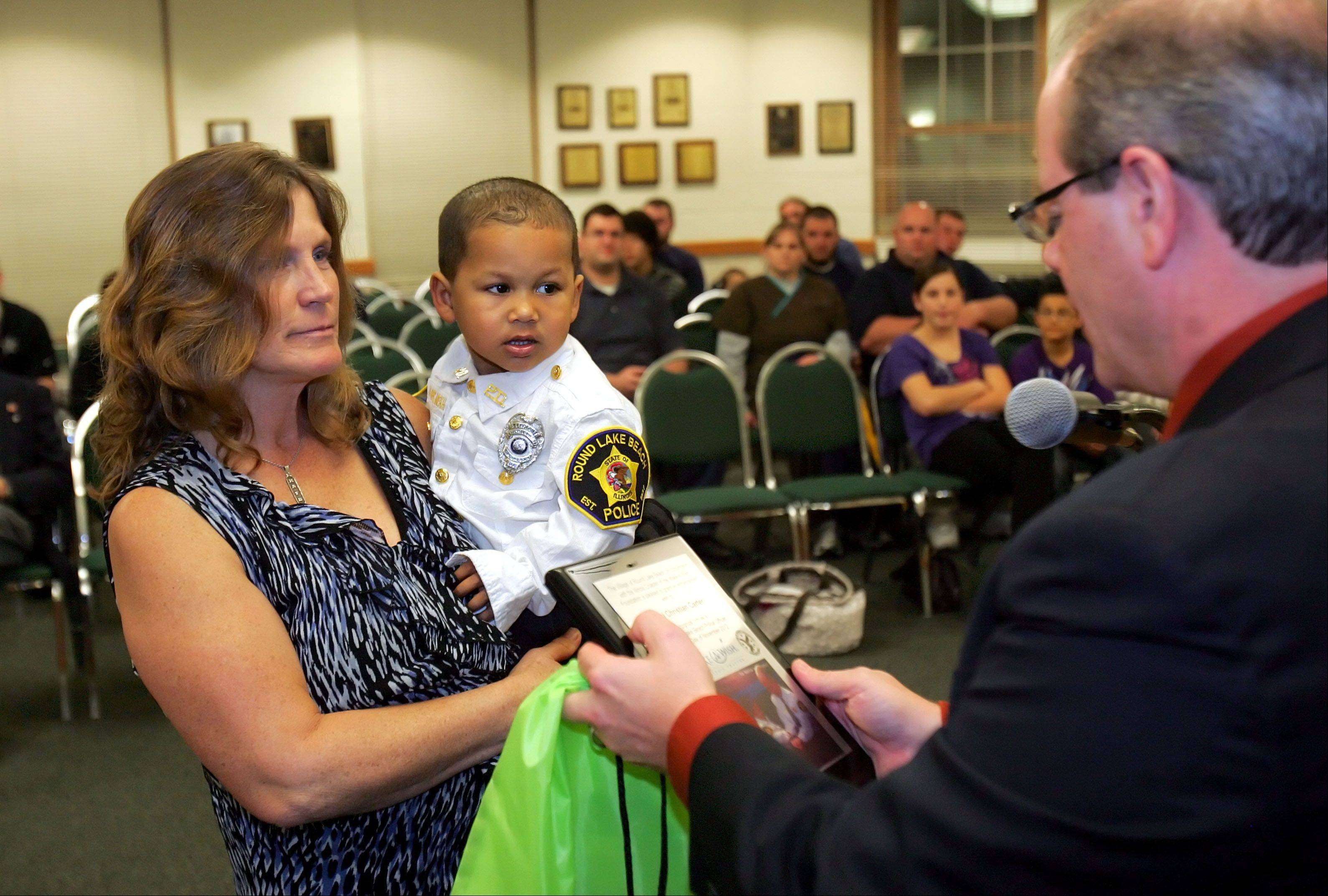 Round Lake Beach Mayor Richard Hill, right, in conjunction with the Illinois Chapter of the Make-A-Wish Foundation, reads a proclamation recognizing Mekhi Carter as a junior village police officer. The Antioch Township boy, who is fascinated with police, has had three open-heart surgeries.