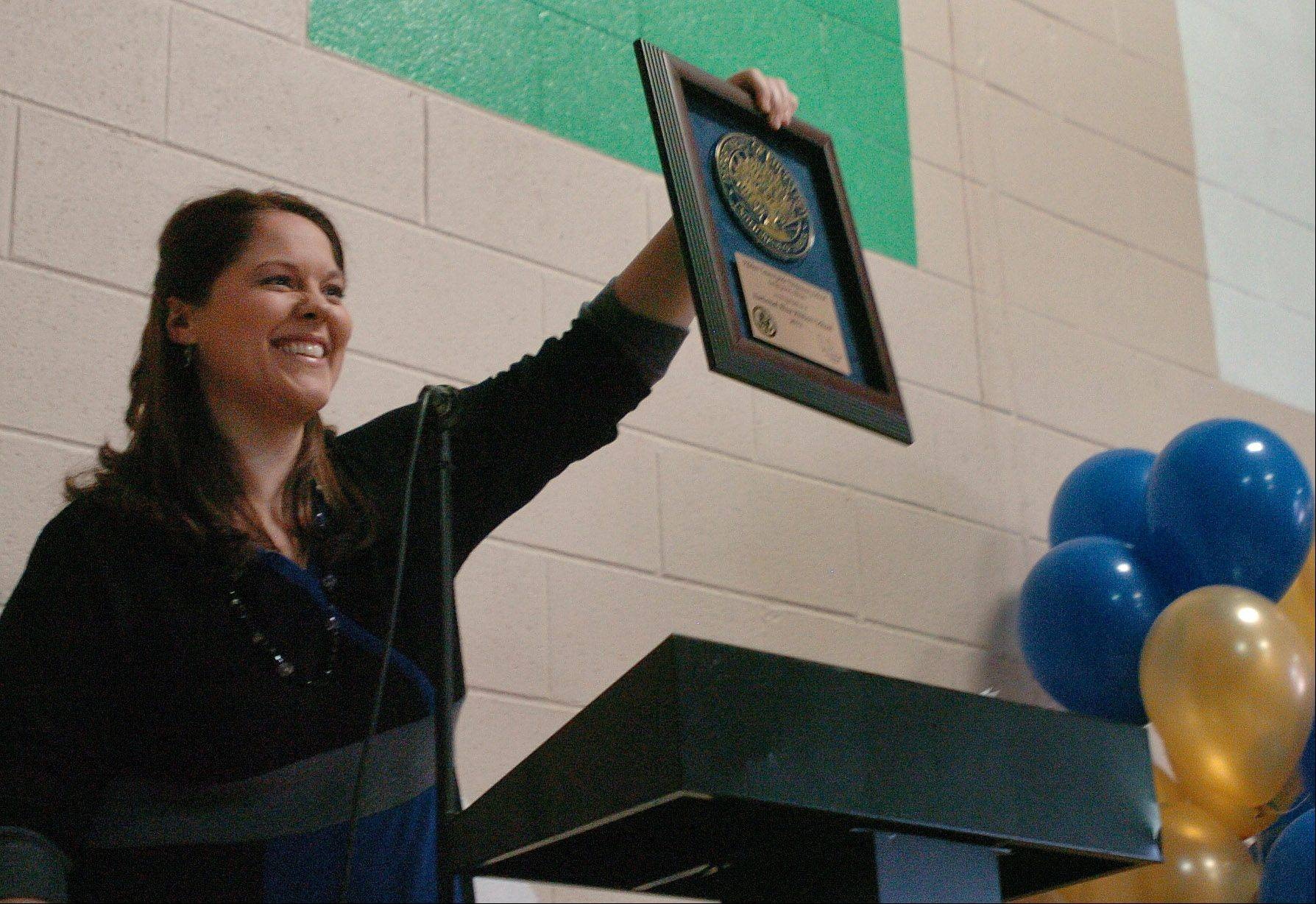 Principal Jennifer Smith holds up the Blue Ribbon plaque, to the delight of assembled students and staff.