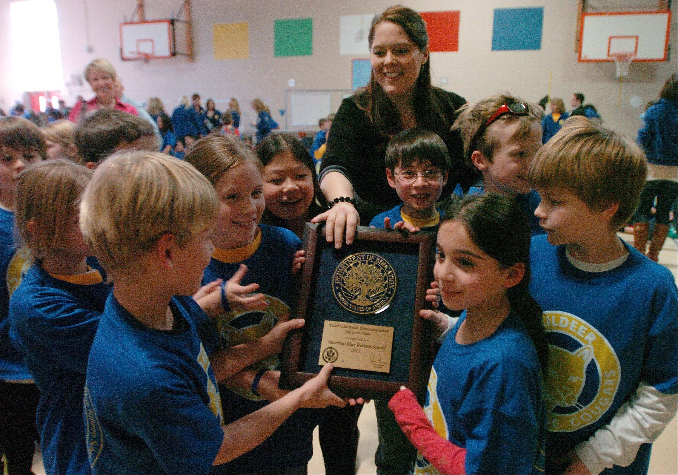 Principal Jennifer Smith passes the plaque among third-graders at the celebration.