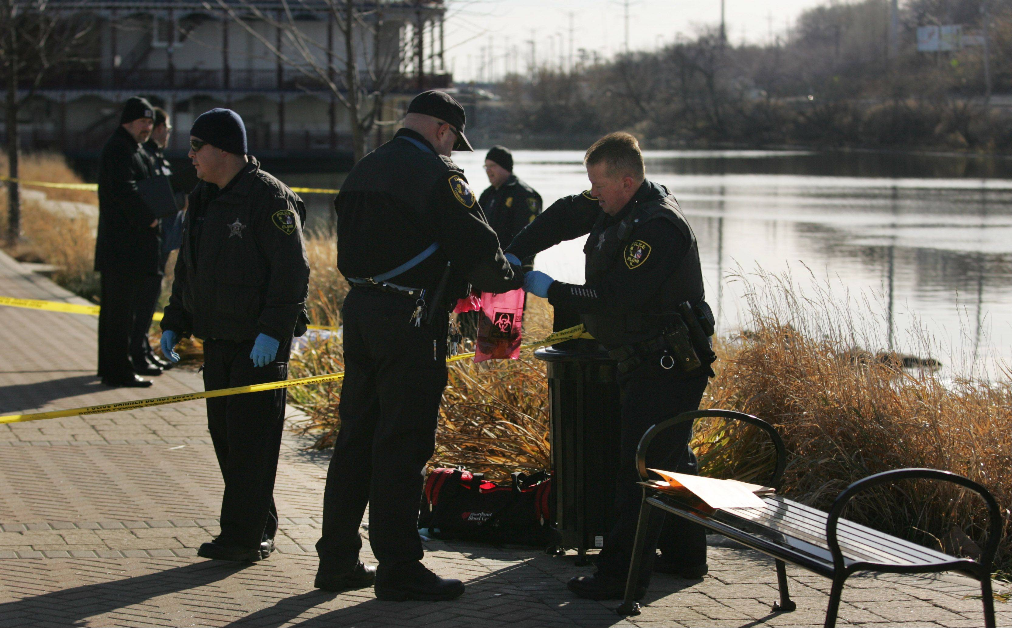 Elgin police evidence technician Mike Gough, right, places some of the belongings of a drowning victim into a bag held by animal control officer James Rog Tuesday along the Fox River near Festival Park in Elgin.
