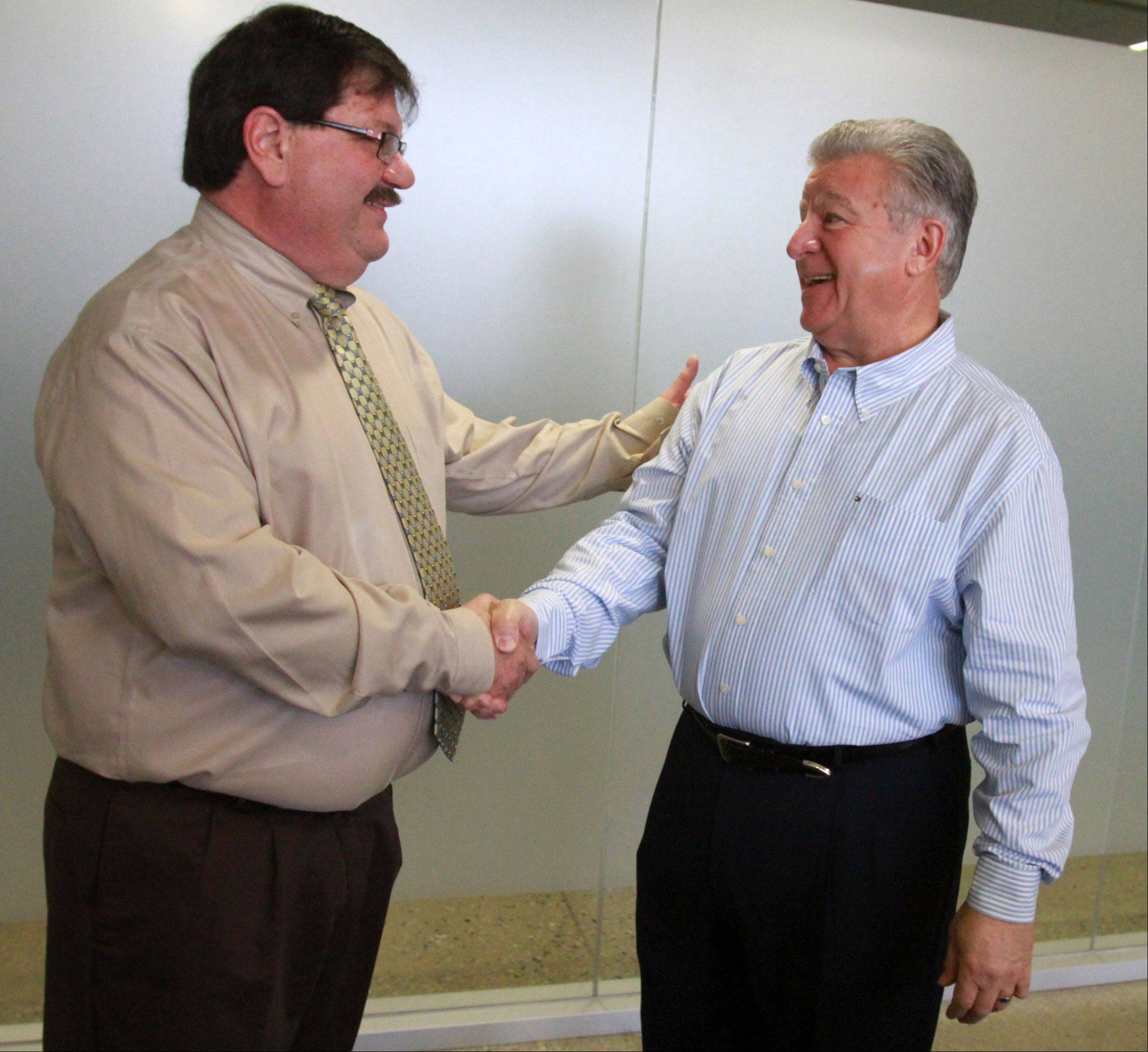 Hanover Park Mayor Rod Craig, left, gets a congratulatory handshake from Carol Stream Village President Frank Saverino after the two weighed in Tuesday morning at the Hanover Park police station community room.