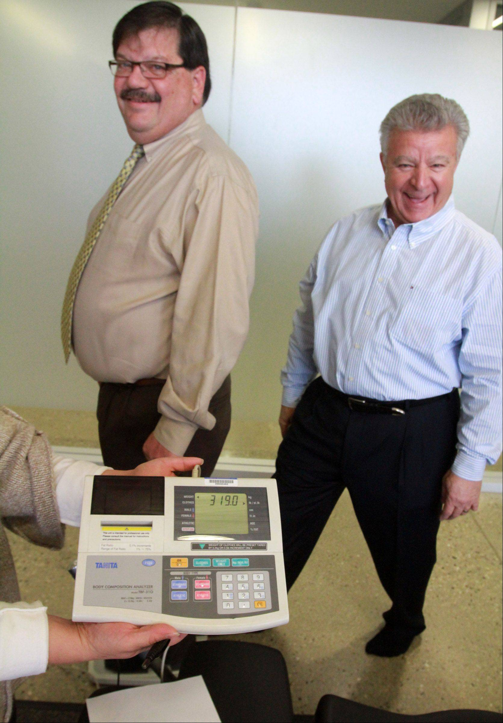 Carol Stream Village President Frank Saverino tries to gain a competitive edge by stepping on the scale as Hanover Park Mayor Rodney Craig completes the final weigh-in of their eight-week weight-loss challenge.