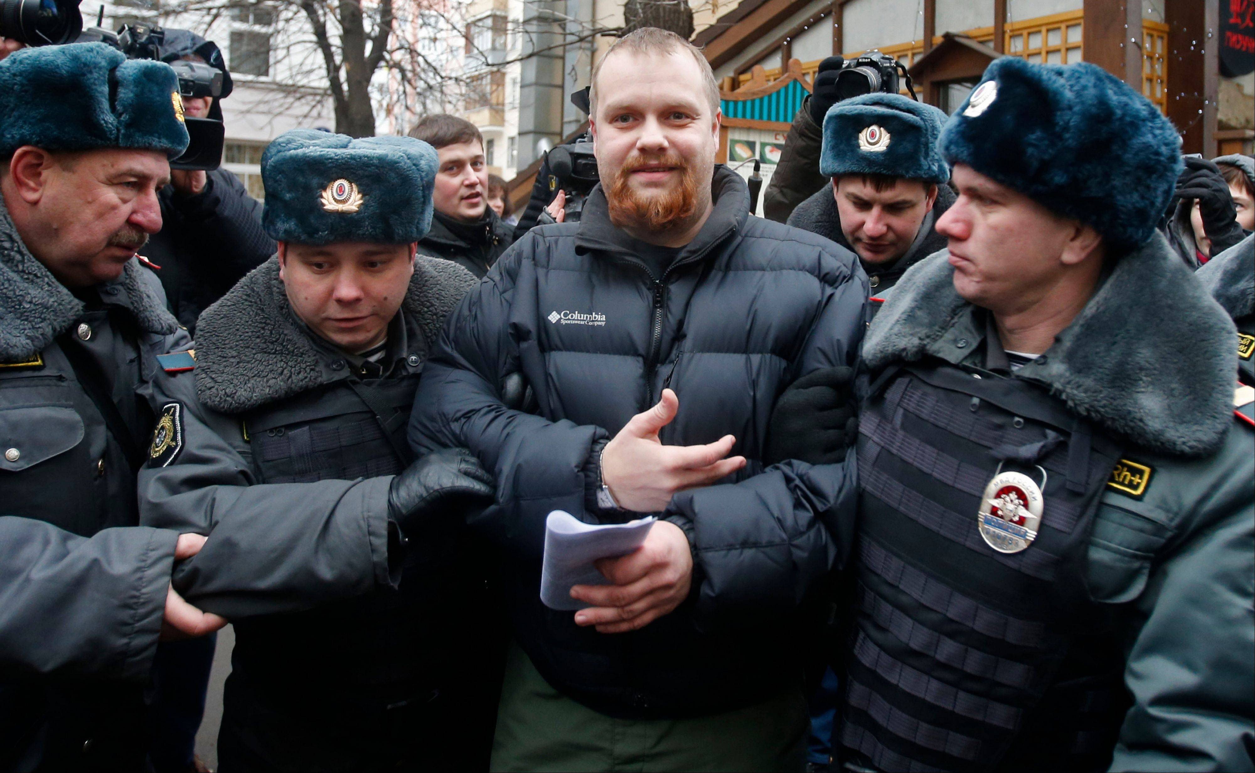 Police officers detain Dmitry Demushkin, the leader of the banned ultranationalist group Slavic Union, outside a court where Russian martial arts champion Rasul Mirzaev was found guilty of involuntary manslaughter, Moscow, Russia, Tuesday, Nov. 27, 2012. Mirzayev was sentenced to two years of house arrest over the death of a man he had punched outside a club.