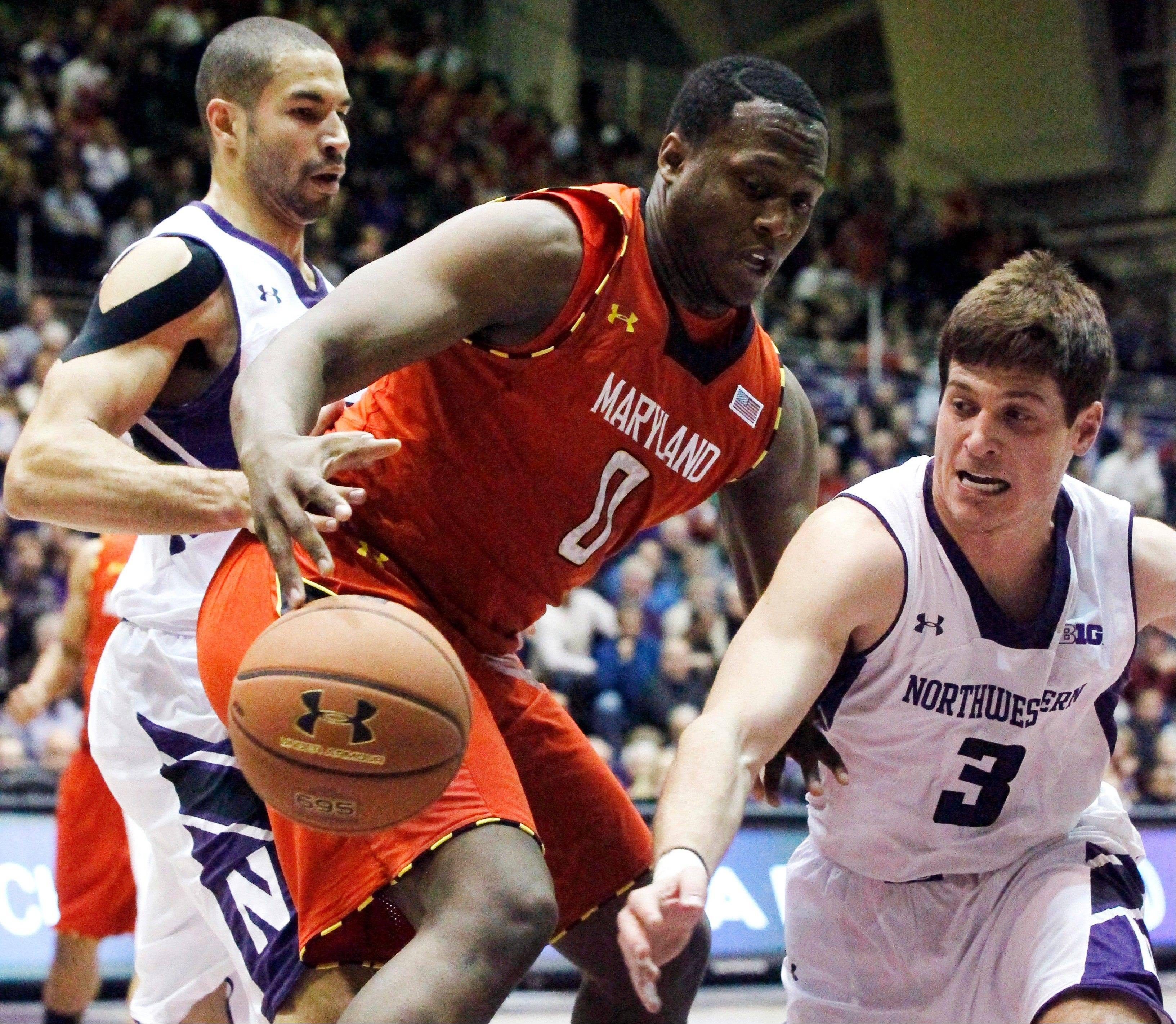 Northwestern guard Dave Sobolewski (3) knocks the ball out of the hands of Maryland forward Charles Mitchell (0) as Northwestern forward Drew Crawford defends Tuesday during the first half in Evanston.