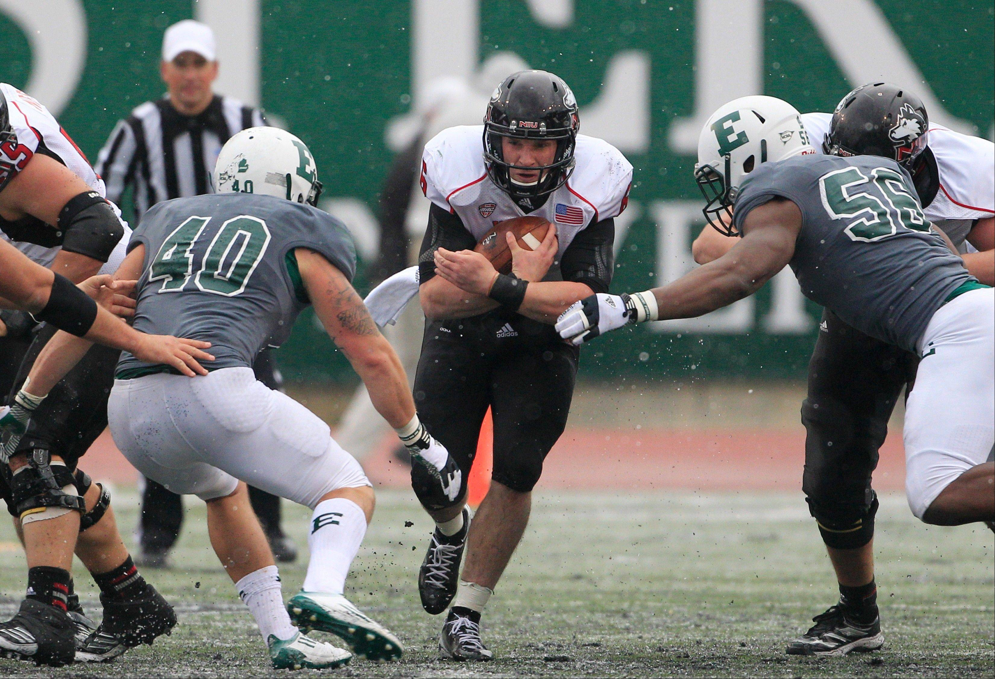 Northern Illinois quarterback Jordan Lynch runs through the defense of Eastern Michigan linebacker Sean Kurtz (40) and defensive lineman Andy Mulumba (56) Friday during the fourth quarter in Ypsilanti, Mich.