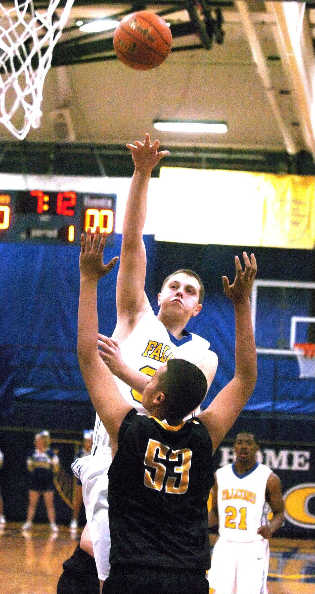 Andrew Zelis of Wheaton North puts up a shot over Barret Benson of Hinsdale South .
