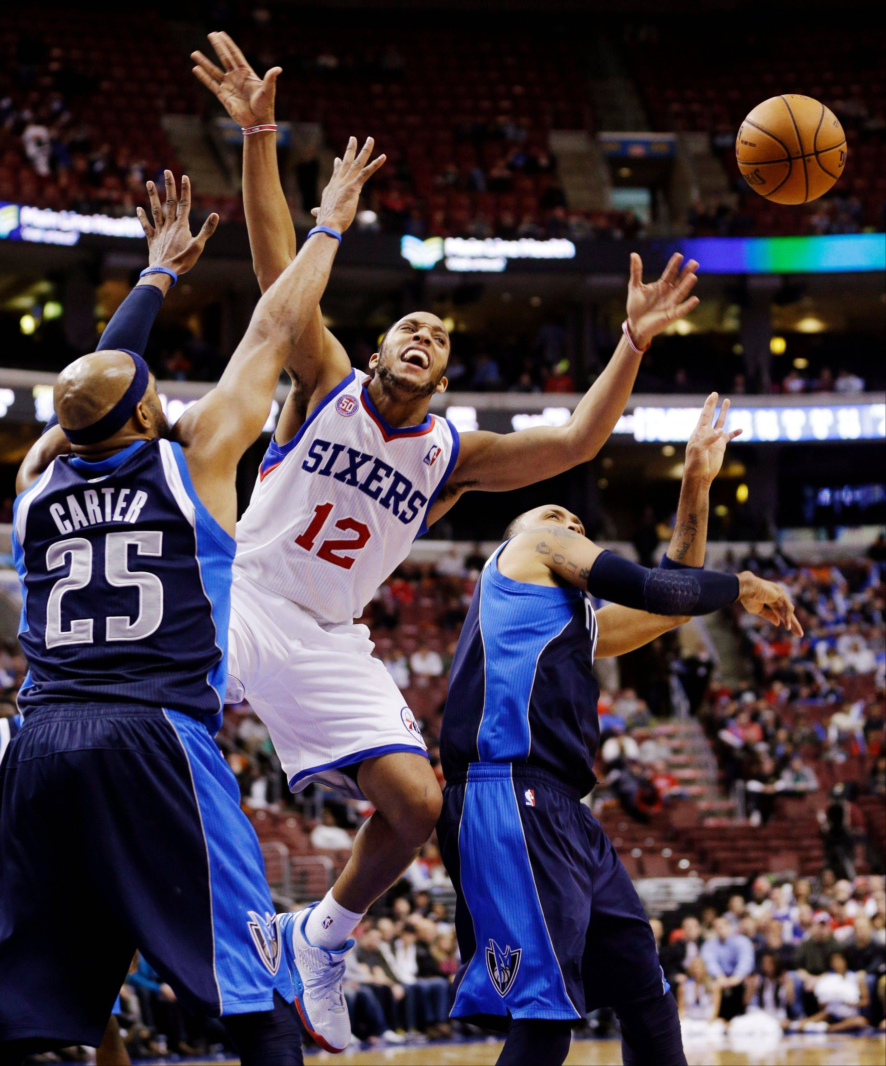 Philadelphia 76ers' Evan Turner, center, loses the ball against Dallas Mavericks' Vince Carter (25) and Shawn Marion Tuesday during the second half in Philadelphia. Philadelphia won 100-98.