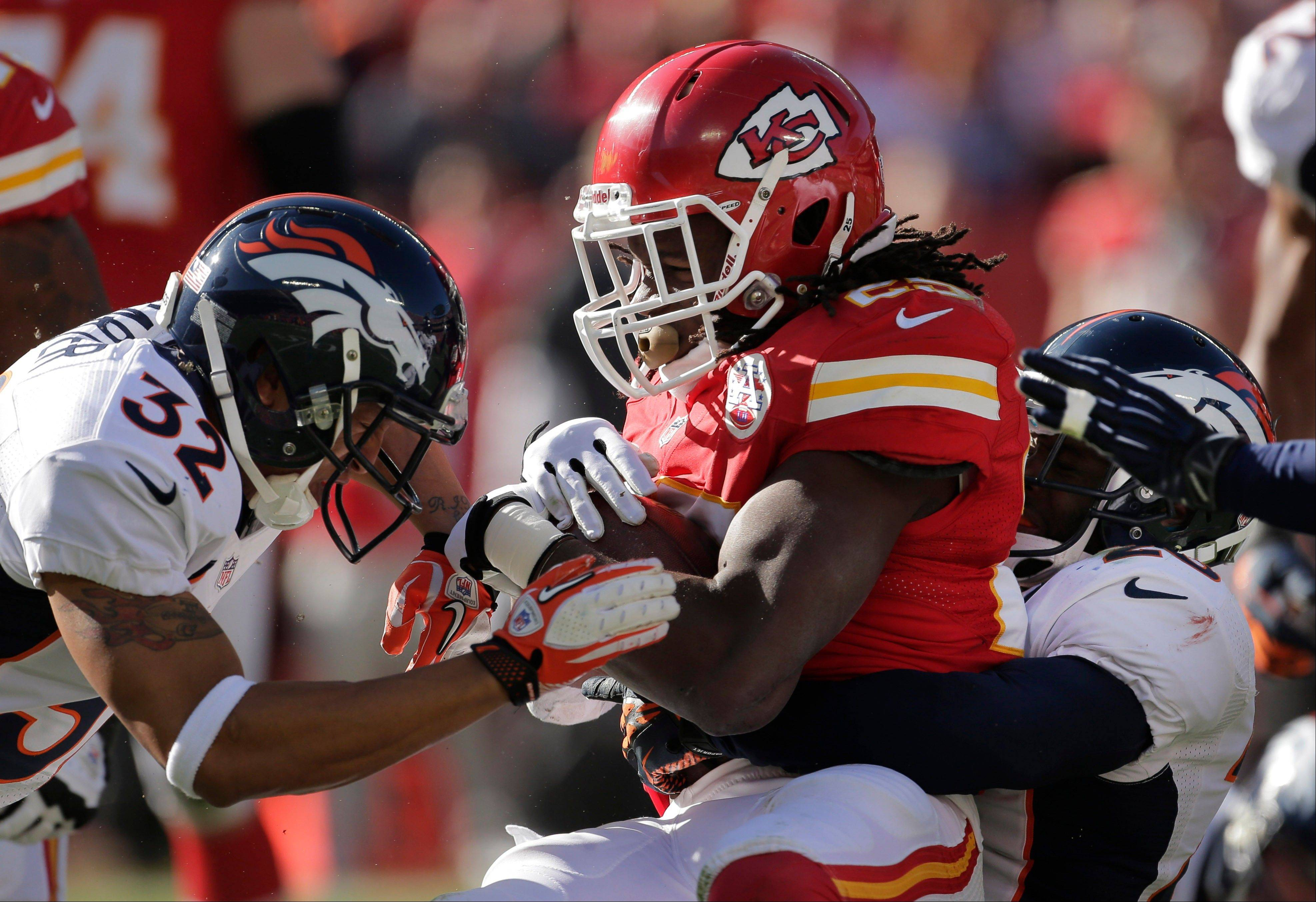 Kansas City Chiefs running back Jamaal Charles is tackled by Denver Broncos strong safety Mike Adams, right, and defensive back Tony Carter (32) Sunday during the first half at Arrowhead Stadium in Kansas City, Mo. harles has caused a stir after asking for Broncos quarterback Peyton Manning's autograph following the game.
