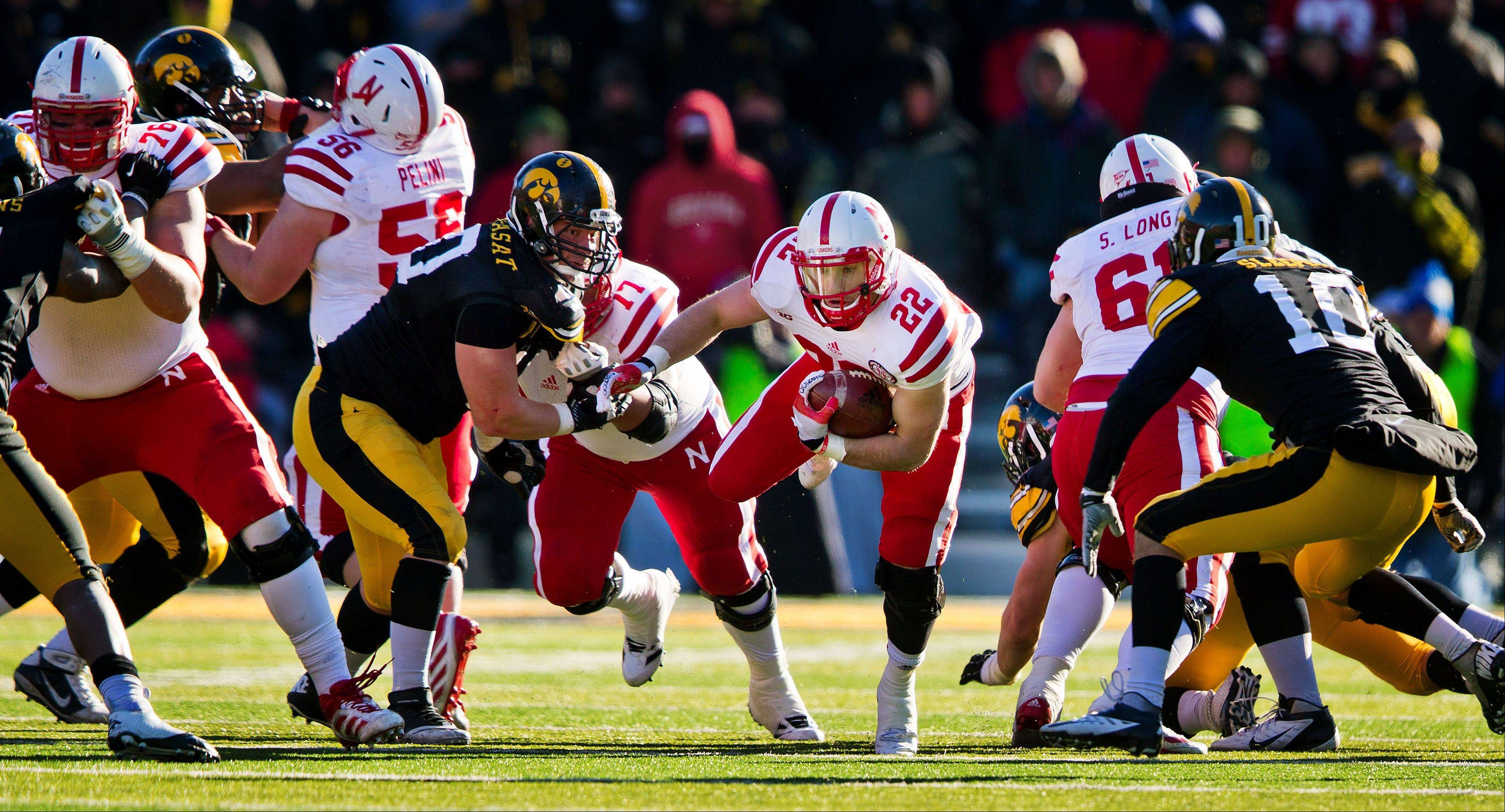 Nebraska's Rex Burkhead (22) runs for a first down with defensive pressure from Iowa's Louis Trinca-Pasat, center left, and Collin Sleeper, right, Friday during the second half in Iowa City, Iowa. Nebraska won 13-7.