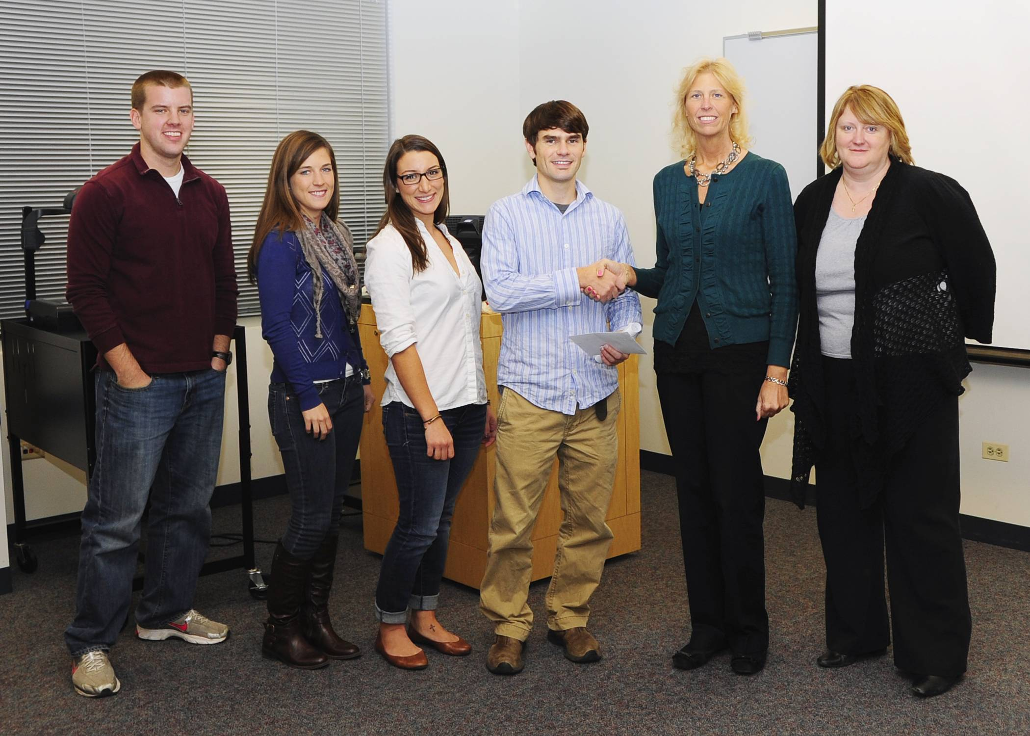 Members of the Sports Medicine Club at Midwestern University present their donation to representatives from the Sharing Connections Furniture Bank.