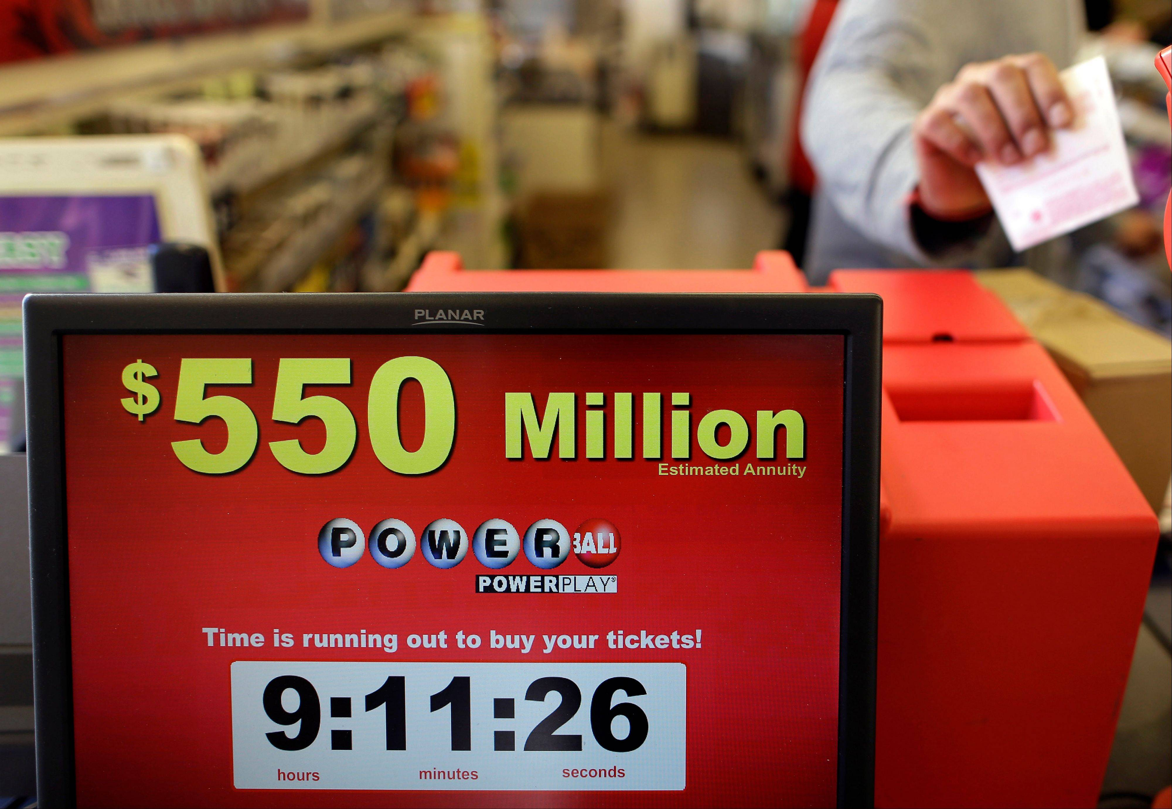 Store clerk Keyur Patel pulls a Powerball ticket dispensed from a machine in a convenience store in Baltimore, Wednesday. There have been no Powerball winners since Oct. 6, and the jackpot has grown into the second highest in lottery history, behind only the $656 million Mega Millions prize in March.