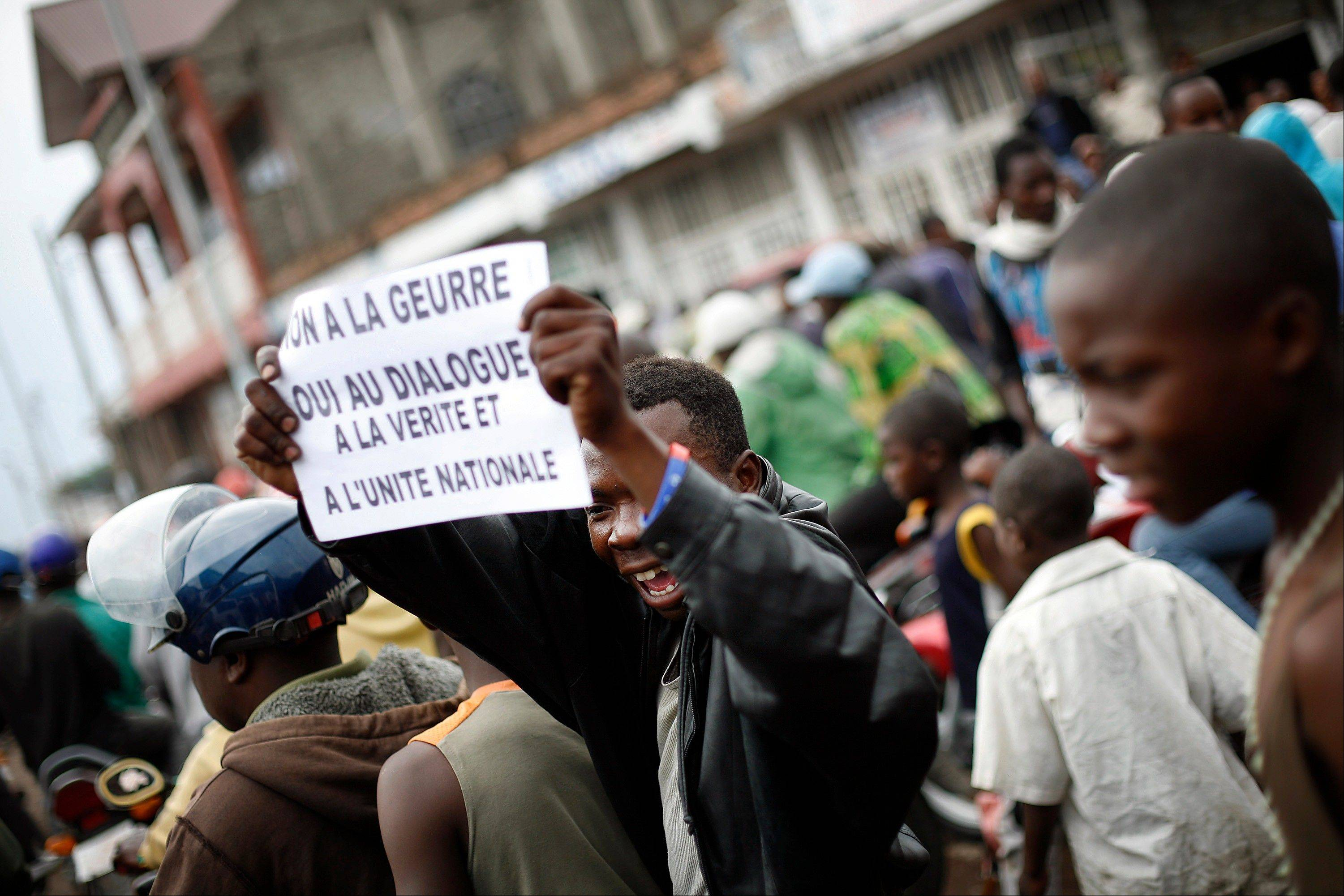 A Goma resident holds up a banner in French reading, �No to war, yes to dialogue, the truth and national unity� as he gathers with others for an anti President Joseph Kabila demonstration supported by the M23 rebel movement in Goma, eastern Congo, Wednesday Nov. 28, 2012.