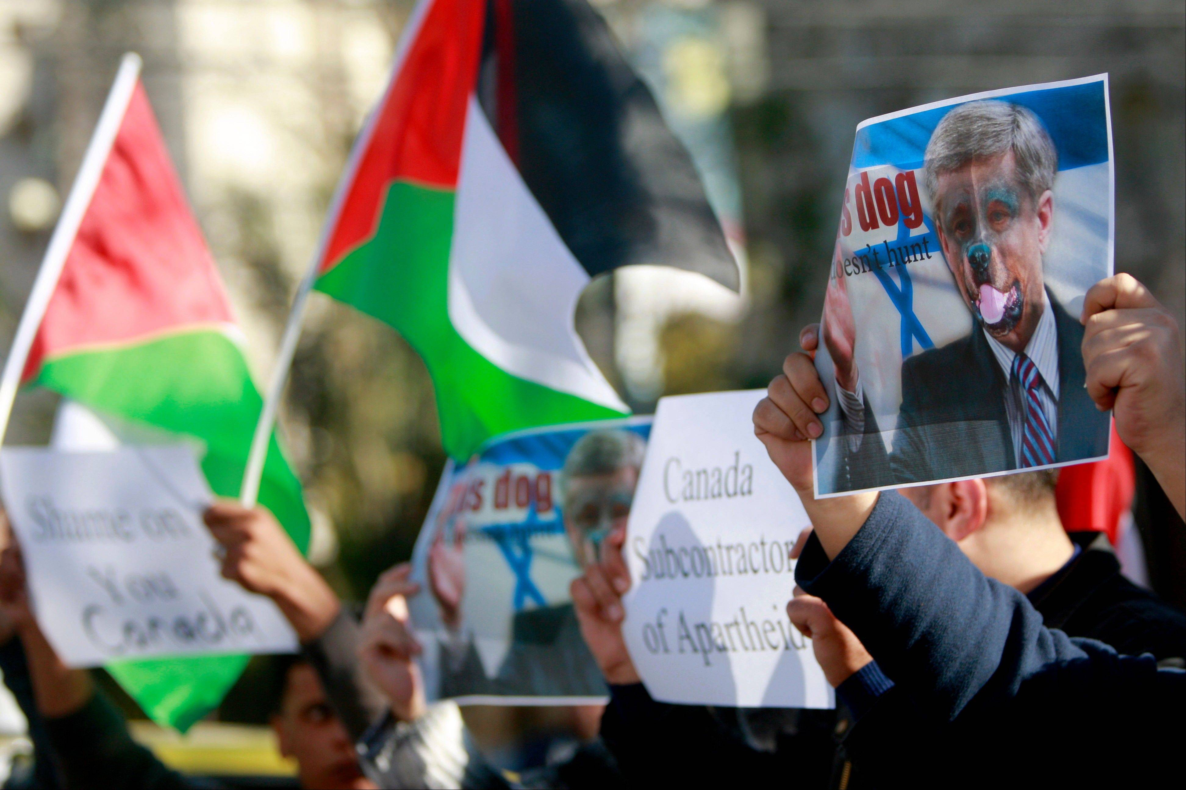 Palestinians hold a Palestinian flag and a poster of Canadian Prime Minister Stephen Harper superimposed with a face of a dog during a protest following his remarks about the Palestinian UN bid for an observer state status, in front of Canadian representative offices in the West bank city of Ramallah, Wednesday, Nov. 28, 2012. Harper has threatened �there will be consequences� if Palestinian Authority President Mahmoud Abbas does not end his campaign for the Palestinian Authority to be recognized by the UN as a nonmember observer state.
