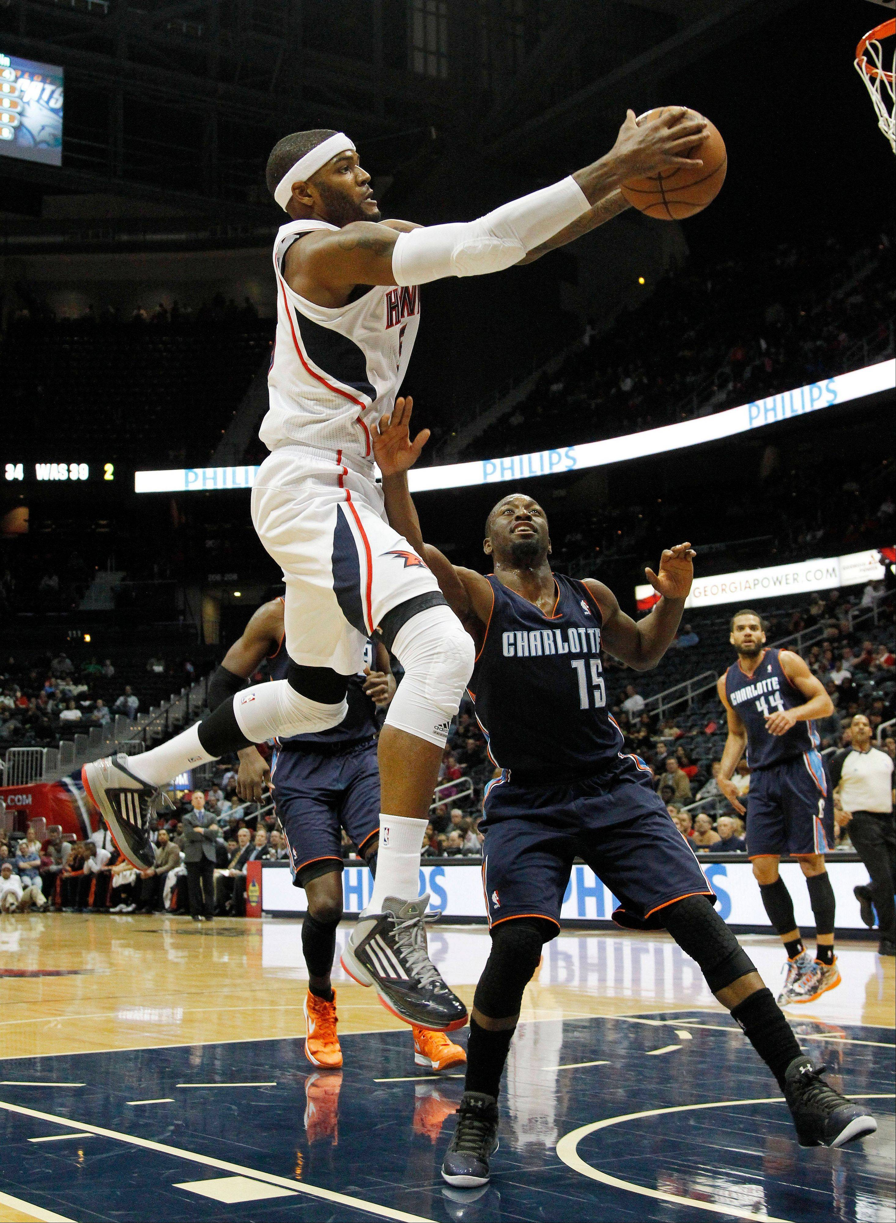 Atlanta Hawks forward Josh Smith goes to the basket as Charlotte Bobcats guard Kemba Walker defends Wednesday during the first half in Atlanta.