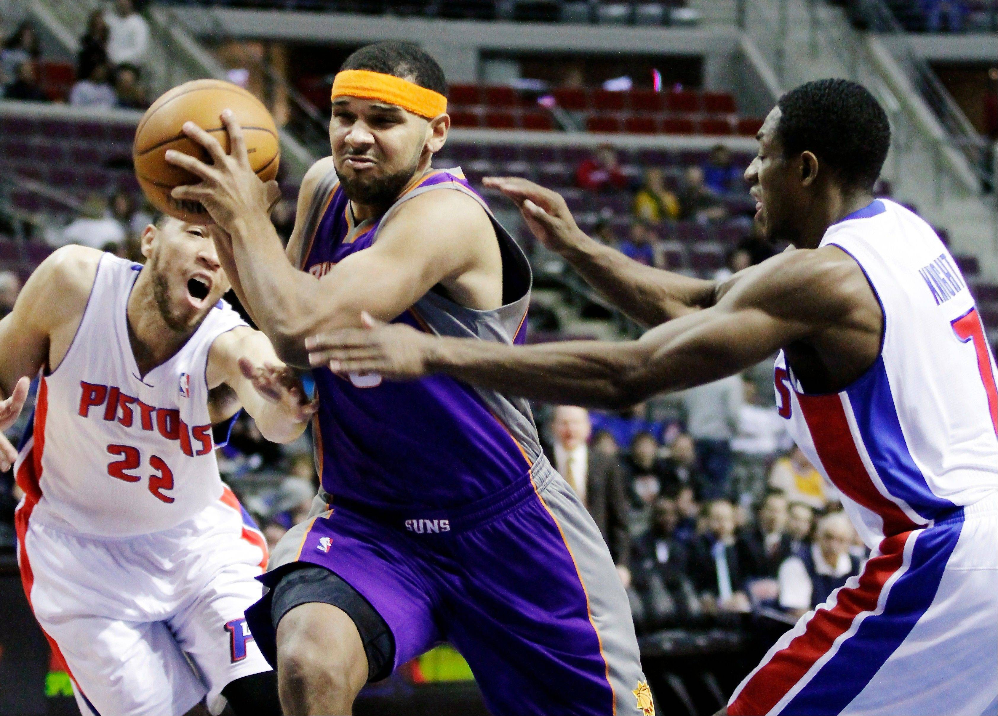 Phoenix Suns guard Jared Dudley drives to the basket between Detroit Pistons forward Tayshaun Prince (22) and guard Brandon Knight (7) Wednesday during the first half in Auburn Hills, Mich.