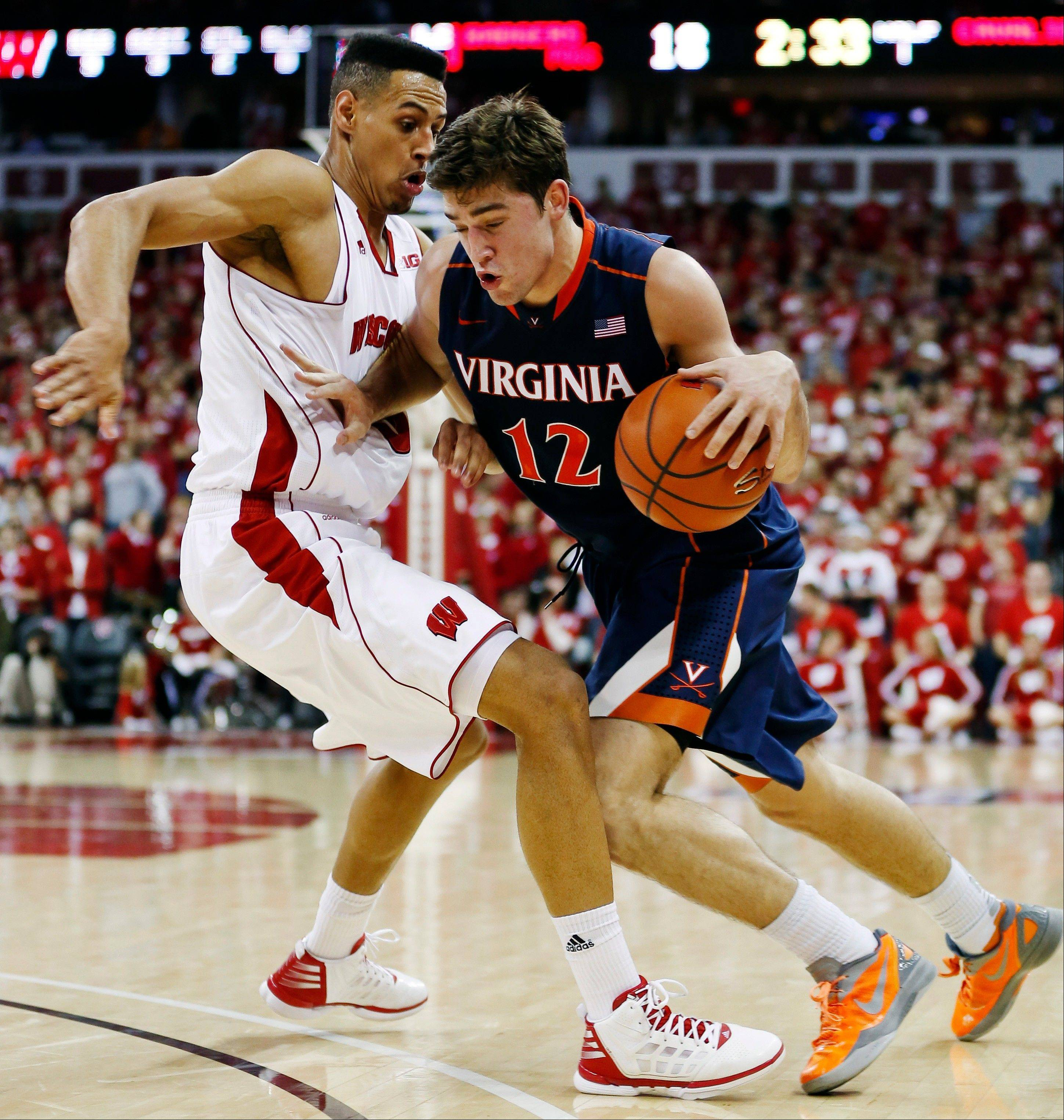 Virginia�s Joe Harris drives on Wisconsin�s Ryan Evans Wednesday during the first half in Madison, Wis.
