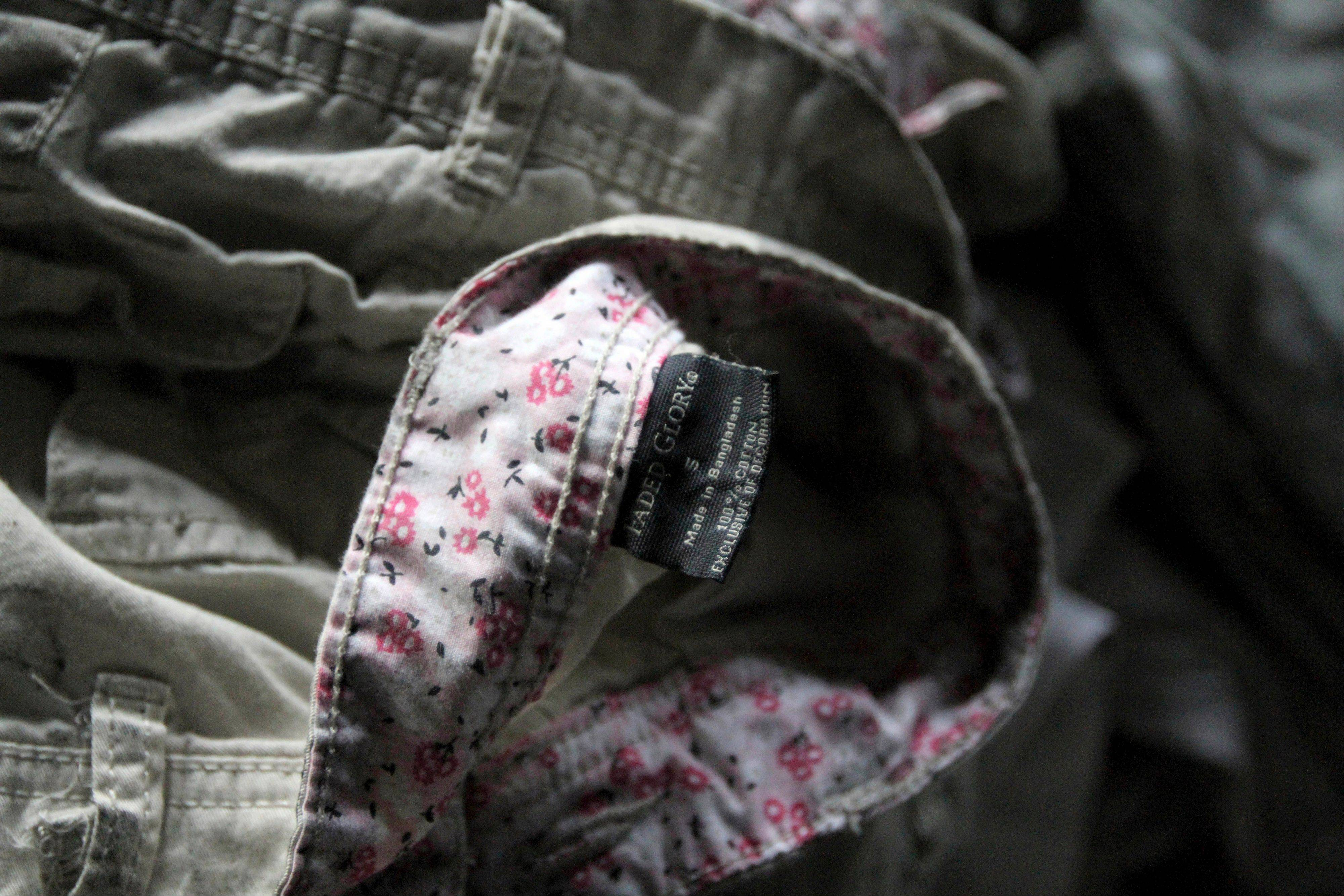 Walmart's Faded Glory label is seen on a piece of clothing laying among equipment charred in the fire that killed 112 workers Saturday at the Tazreen Fashions Ltd. factory, on the outskirts of Dhaha, Bangladesh, Wednesday, Nov. 28, 2012.