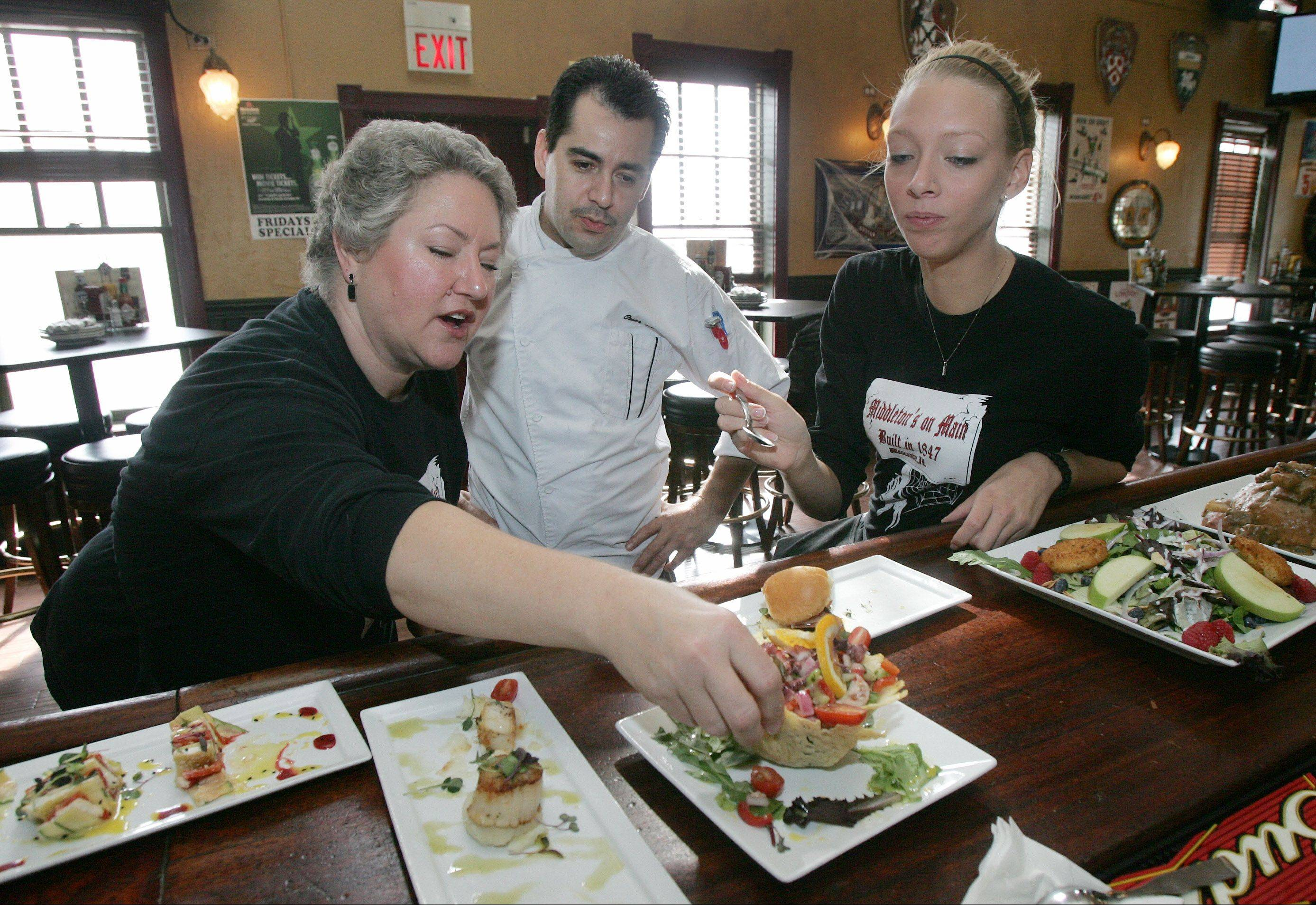 Servers Marcia Lecheler, left, and Chelsea Hanson sample tapas created by Chef Cesar Herrera, center, before lunch at Middleton's On Main restaurant in Wauconda.