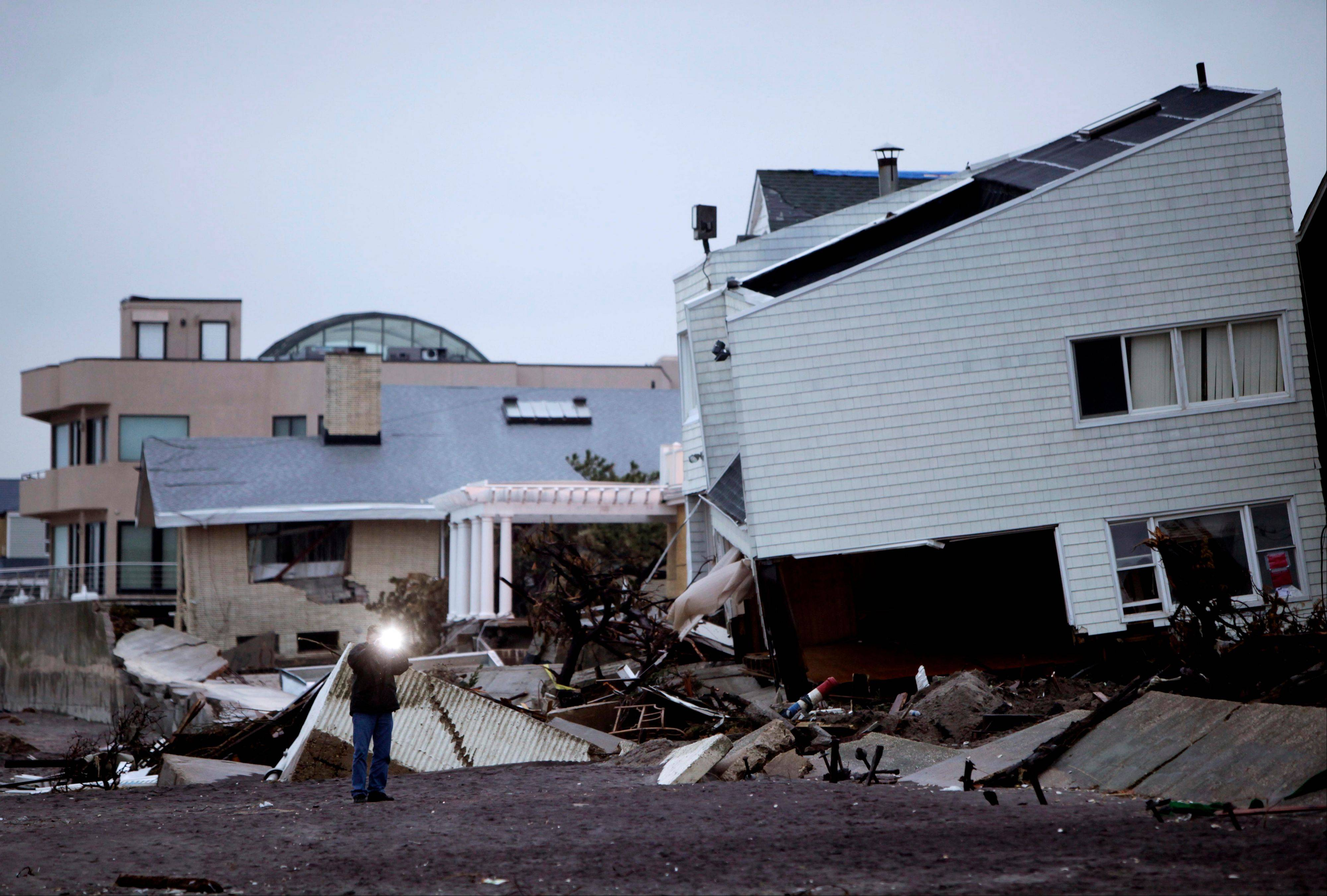A man takes a picture of destroyed homes on the Rockaway Peninsula in Queens, New York, Tuesday.