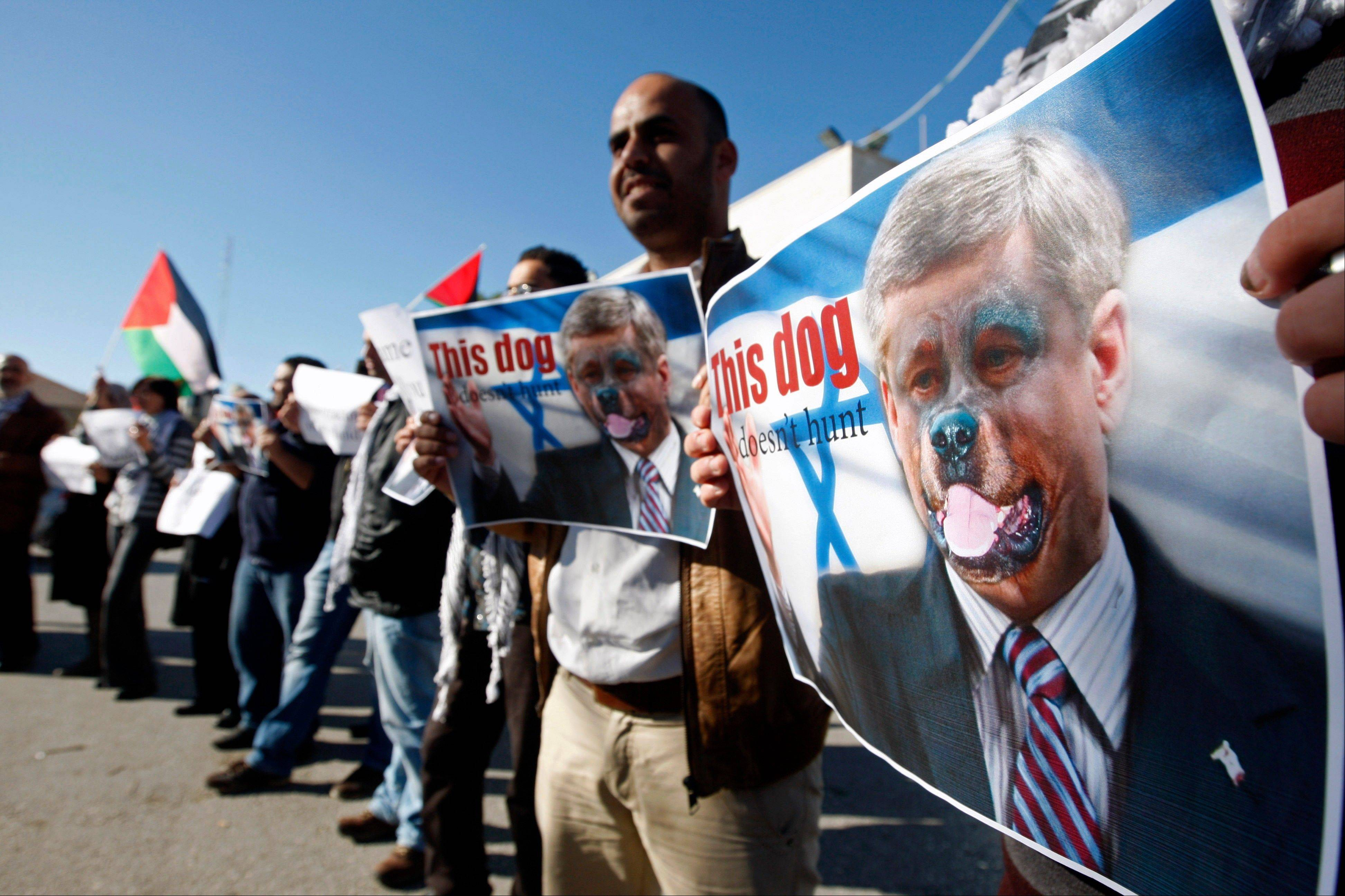 "Palestinians hold pictures of Canadian Prime Minister Stephen Harper superimposed with a face of a dog during a protest following his remarks about the Palestinian UN bid for an observer state status, in front of Canadian representative offices in the West bank city of Ramallah, Wednesday. Harper has threatened ""there will be consequences"" if Palestinian Authority President Mahmoud Abbas does not end his campaign for the Palestinian Authority to be recognized by the UN as a non-member observer state."