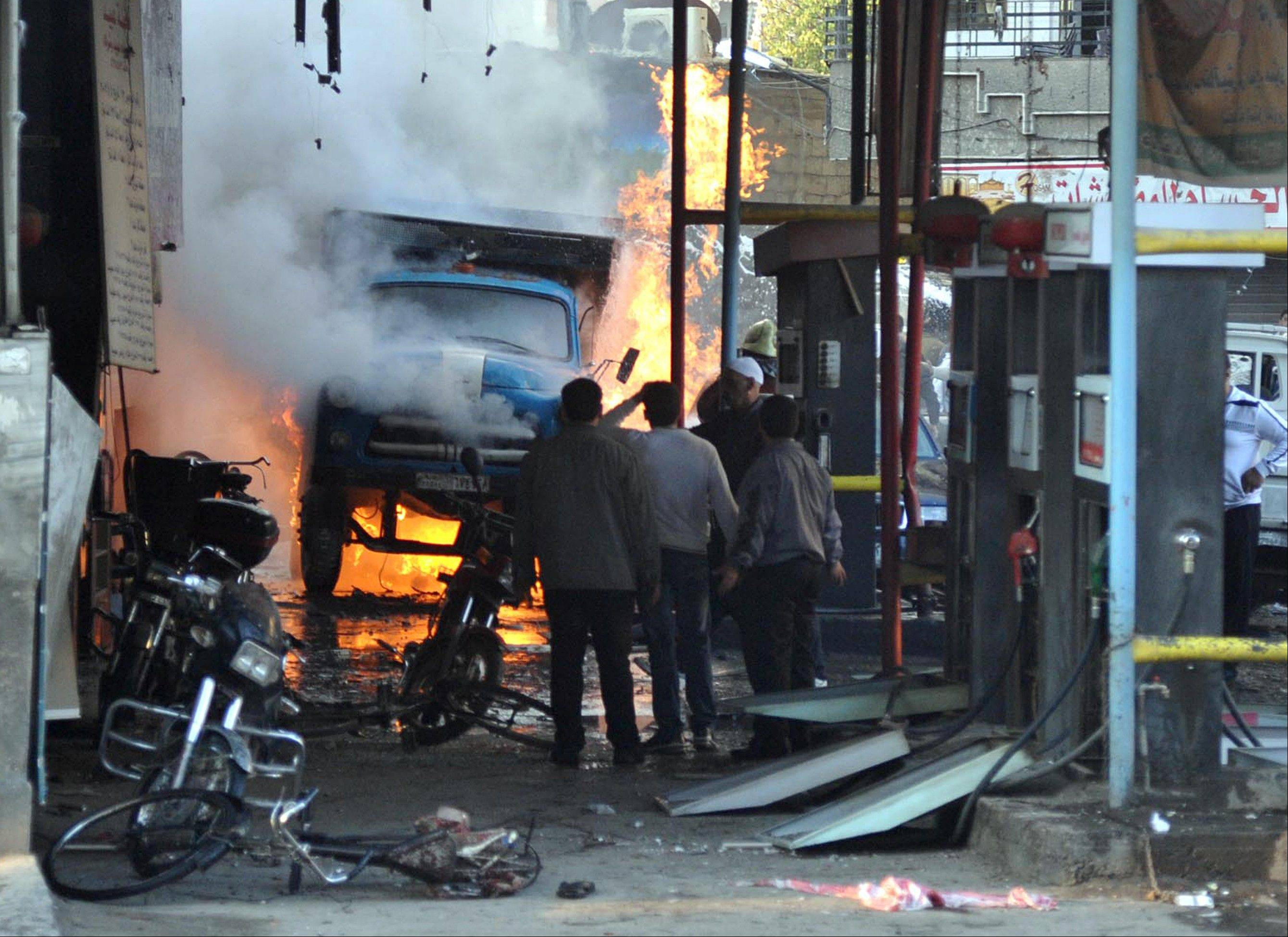 In this photo released by the Syrian official news agency SANA, Syrian citizens stand near a burning truck that was destroyed by two cars bombs, at Jaramana neighborhood, in the suburb of Damascus, S