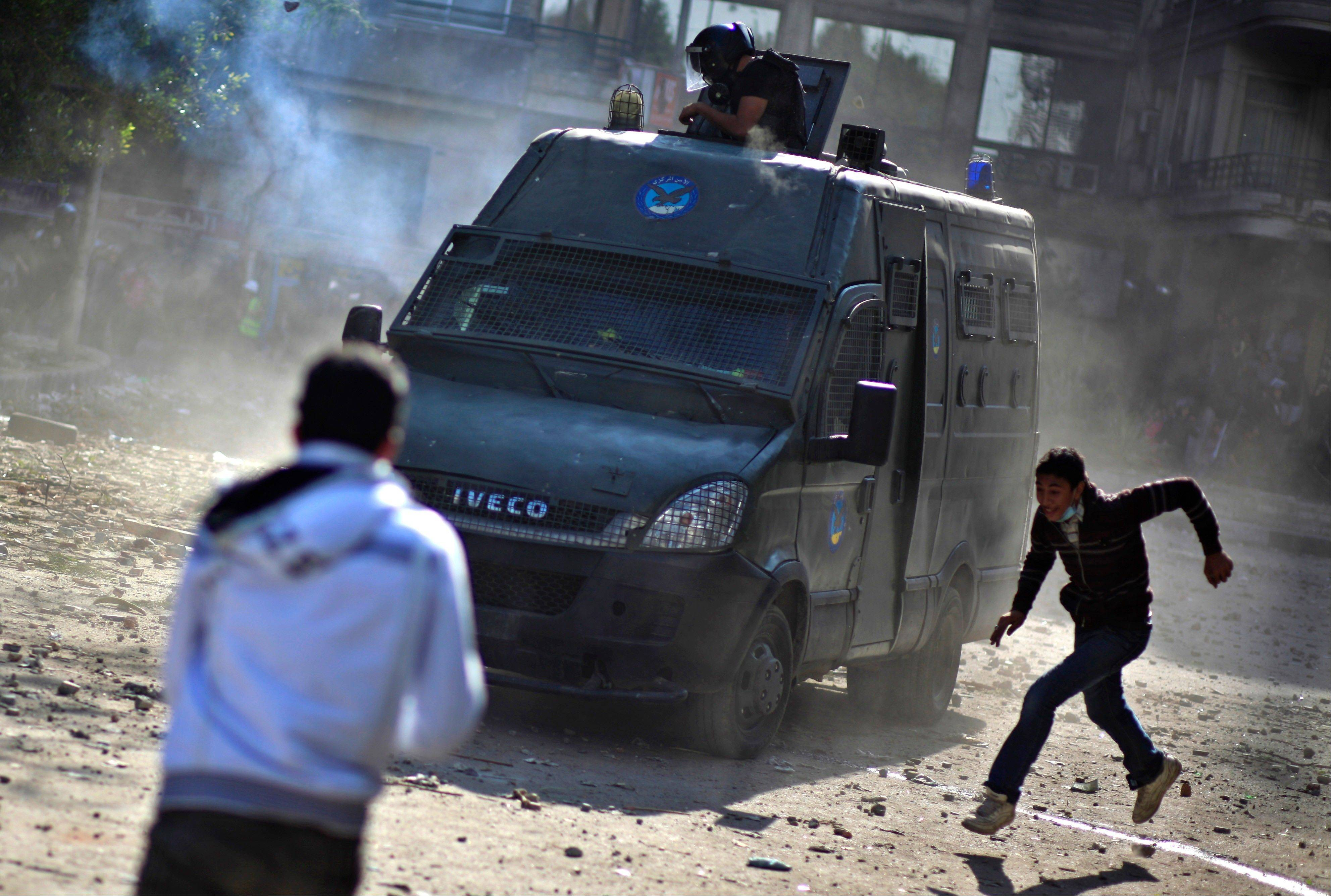 Egyptian protesters clash with security forces near Tahrir Square, in Cairo Wednesday. Egyptian state television says the country's highest appeal court has decided to suspend its work nationwide to protest the president's decrees giving himself nearly absolute powers.