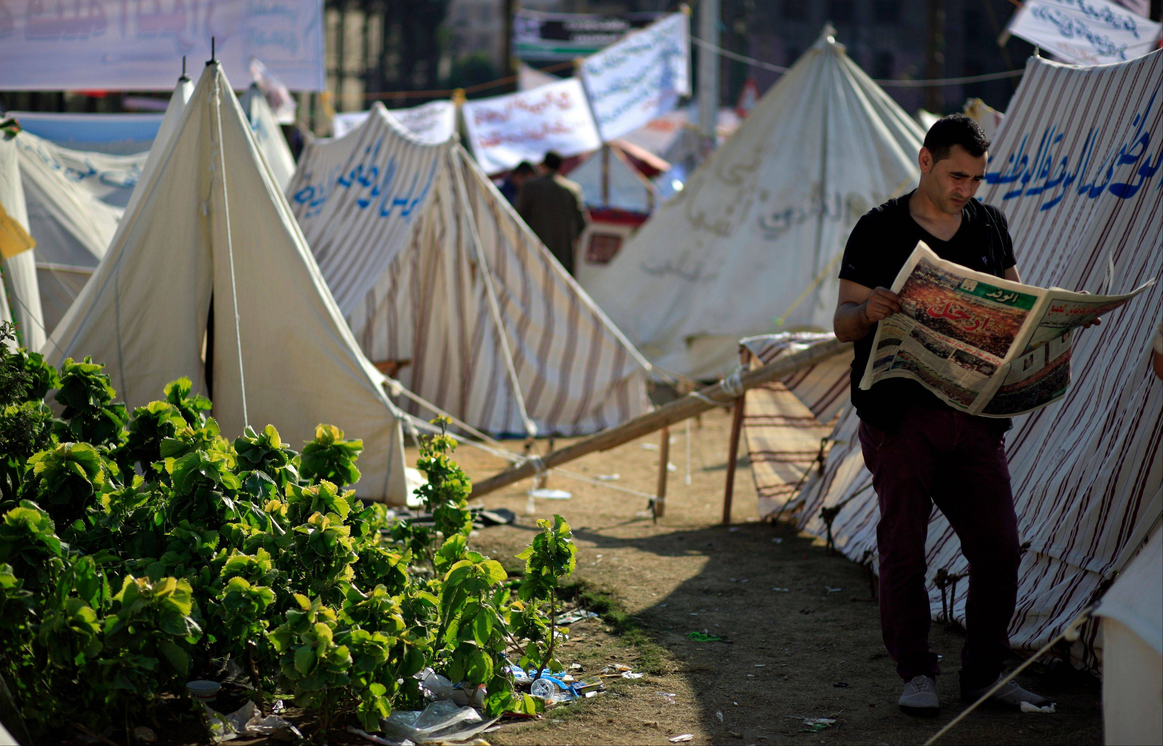 An Egyptian protester reads the Wafd, a local newspaper next to tents occupied by protesters in Tahrir Square, in Cairo Wednesday. Egyptian state television says the country's highest appeal court has decided to suspend its work nationwide to protest the president's decrees giving himself nearly absolute powers.
