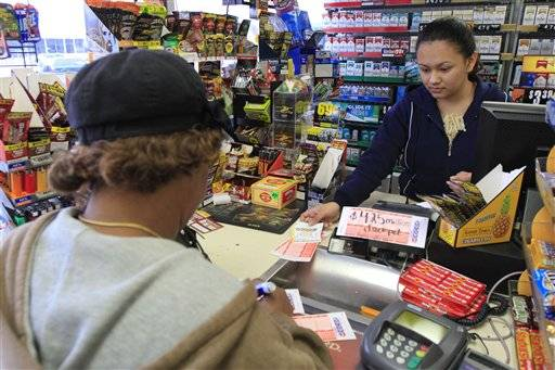Roselyn Jones purchases a few Powerball tickets from station attendant Claudia Molina at the Conoco Sunrise Market  in Chattanooga, Tenn. The historic Powerball jackpot boosted to $550 million on Wednesday and could go higher.