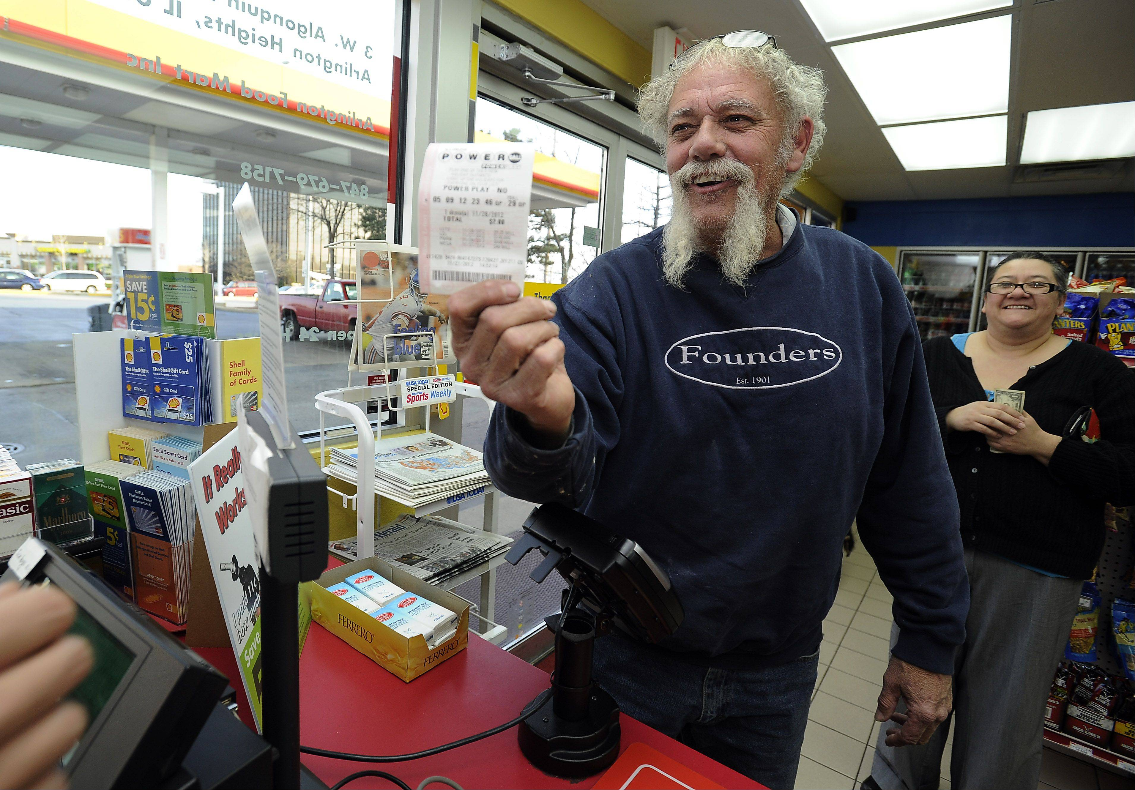Mark Welsh/mwelsh@dailyherald.comDoug O'Keefe of Arlington Heights just purchased his 425 million powerball winning ticket, (he hopes) from Shell gas station clerk Marko Stojiljkovic on Tuesday, one day before the big drawing.