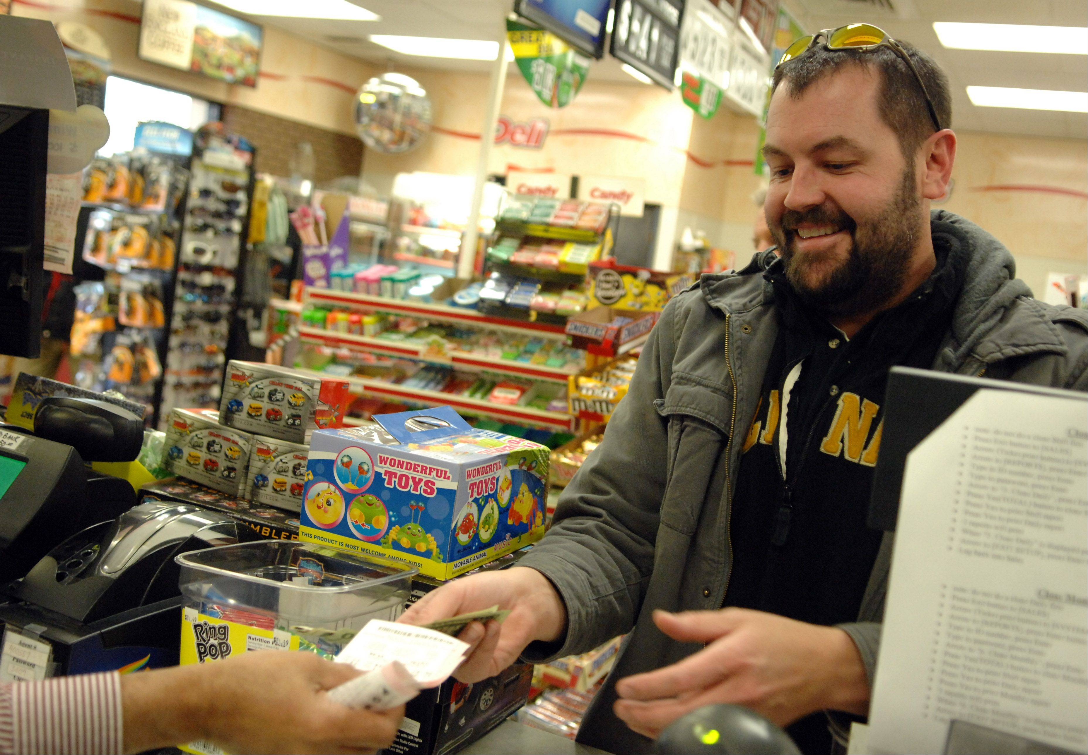 "Brian Bone of Elgin buys $24 worth of Powerball tickets at the Citgo station on Larkin Avenue in Elgin Tuesday. Bone said he buys tickets ""only when it gets this big."""