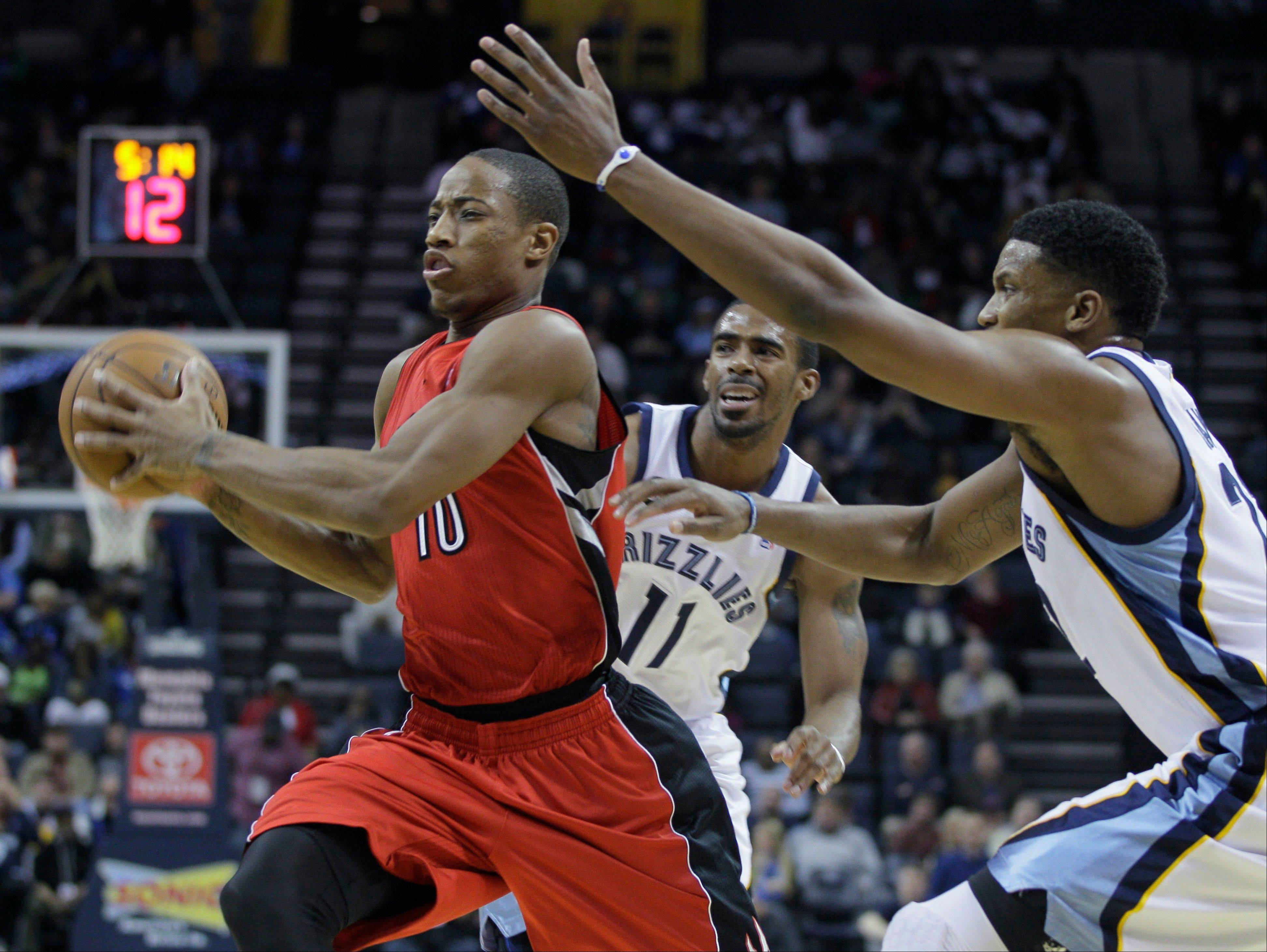 The Toronto Raptors' DeMar DeRozan (10) eludes the Memphis Grizzlies' Mike Conley (11) and Rudy Gay, right, Wednesday during the first half in Memphis, Tenn.