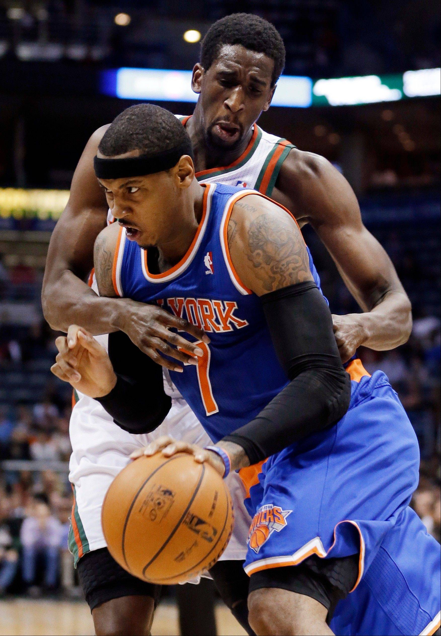 New York Knicks forward Carmelo Anthony is fouled by Milwaukee Bucks' Ekpe Udoh as he drives Wednesday during the first half in Milwaukee.