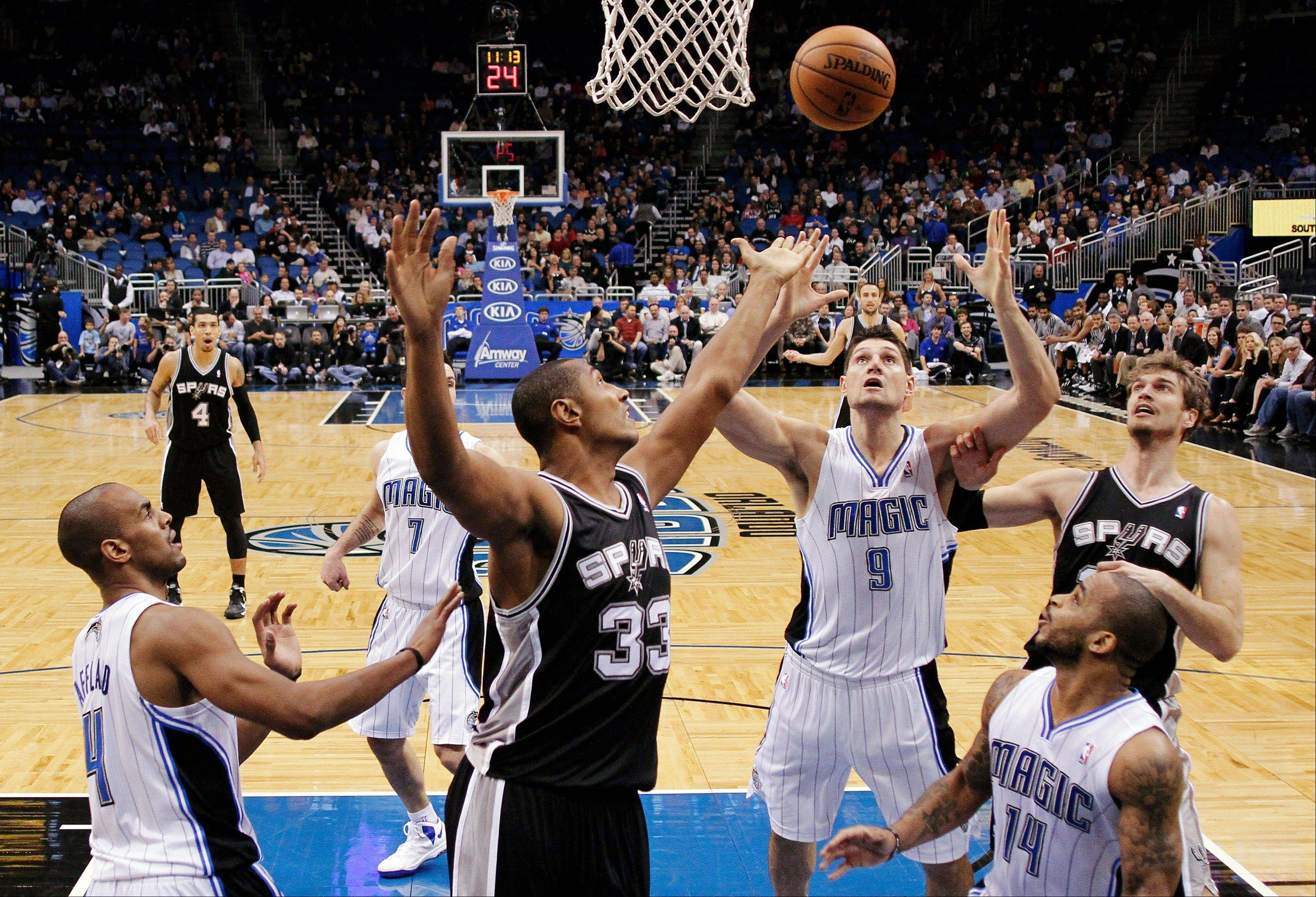 The San Antonio Spurs' Boris Diaw (33) battles for a rebound with Orlando Magic's Nikola Vucevic (9) as Arron Afflalo (4) and Jameer Nelson (14) watch Wednesday during the first half in Orlando, Fla.