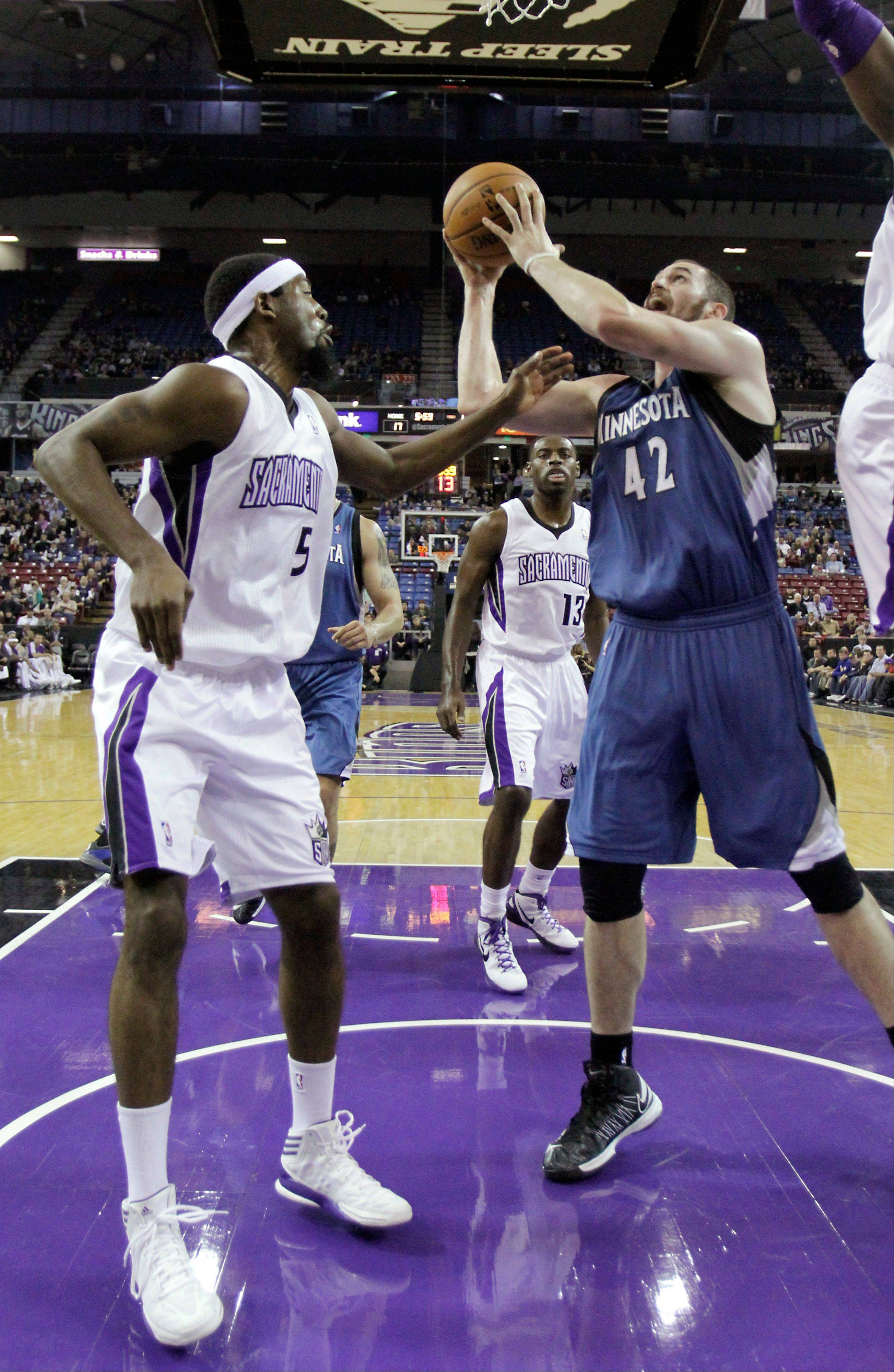 Minnesota Timberwolves forward Kevin Love, right, shoots against Sacramento Kings forward John Salmons, left, Tuesday during the first quarter in Sacramento, Calif.