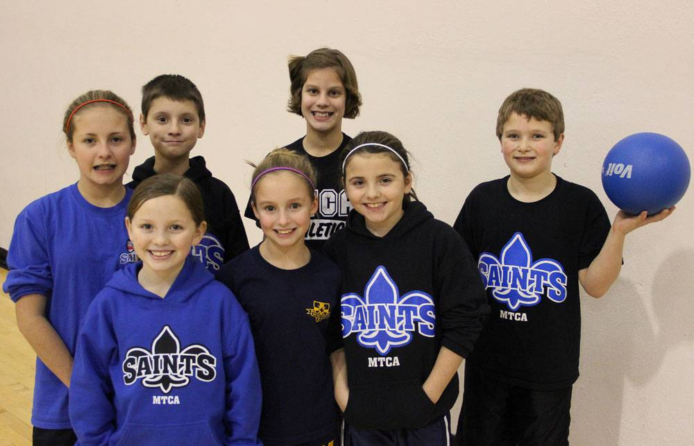 A youth dodgeball team from last year's Winter Nationals pose with a dodgeball.