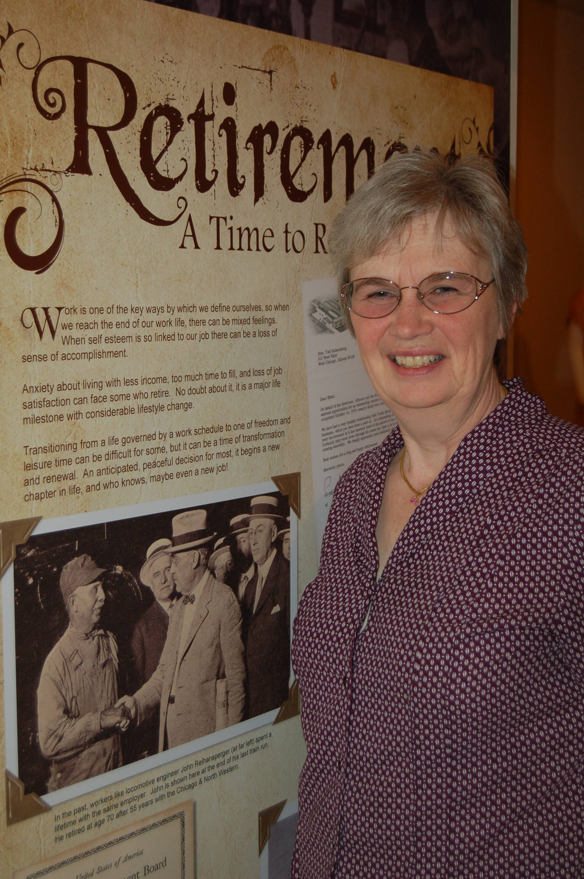 Aptly positioned in front of an exhibit (Rites of Passage) panel depicting retirement, LuAnn Bombard approaches a milestone in her own life - retirement from a 26-year career at the City of West Chicago.