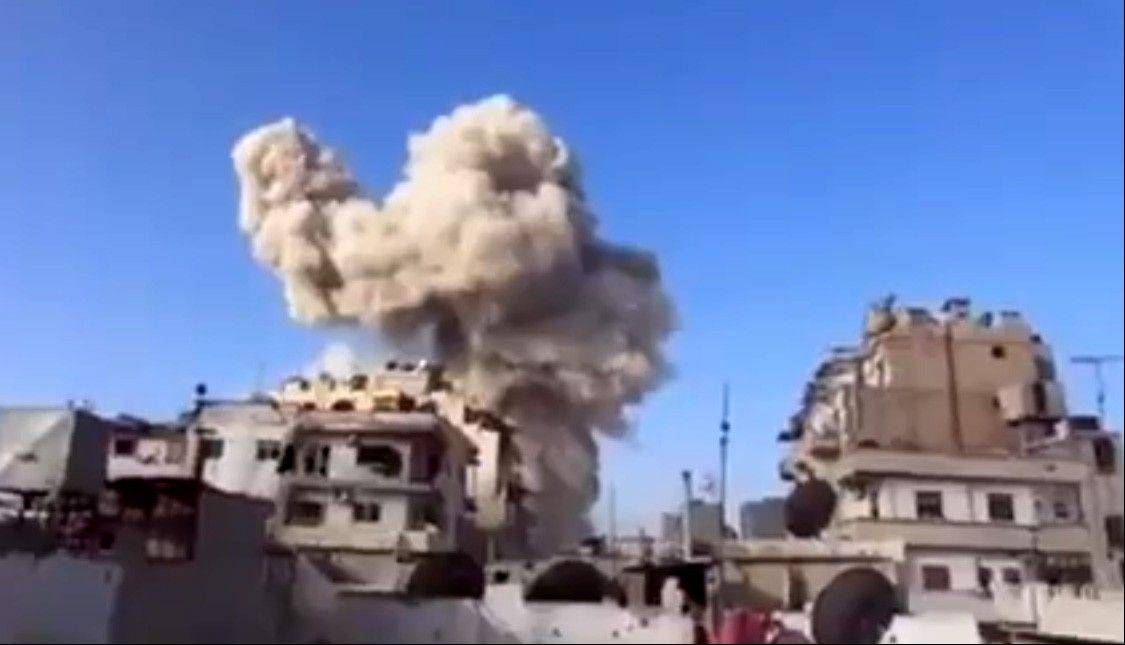 In this image taken from video obtained from the Ugarit News, which has been authenticated based on its contents and other AP reporting, smoke leaps the air from a building after a warplane attack in Homs, Syria, Wednesday.