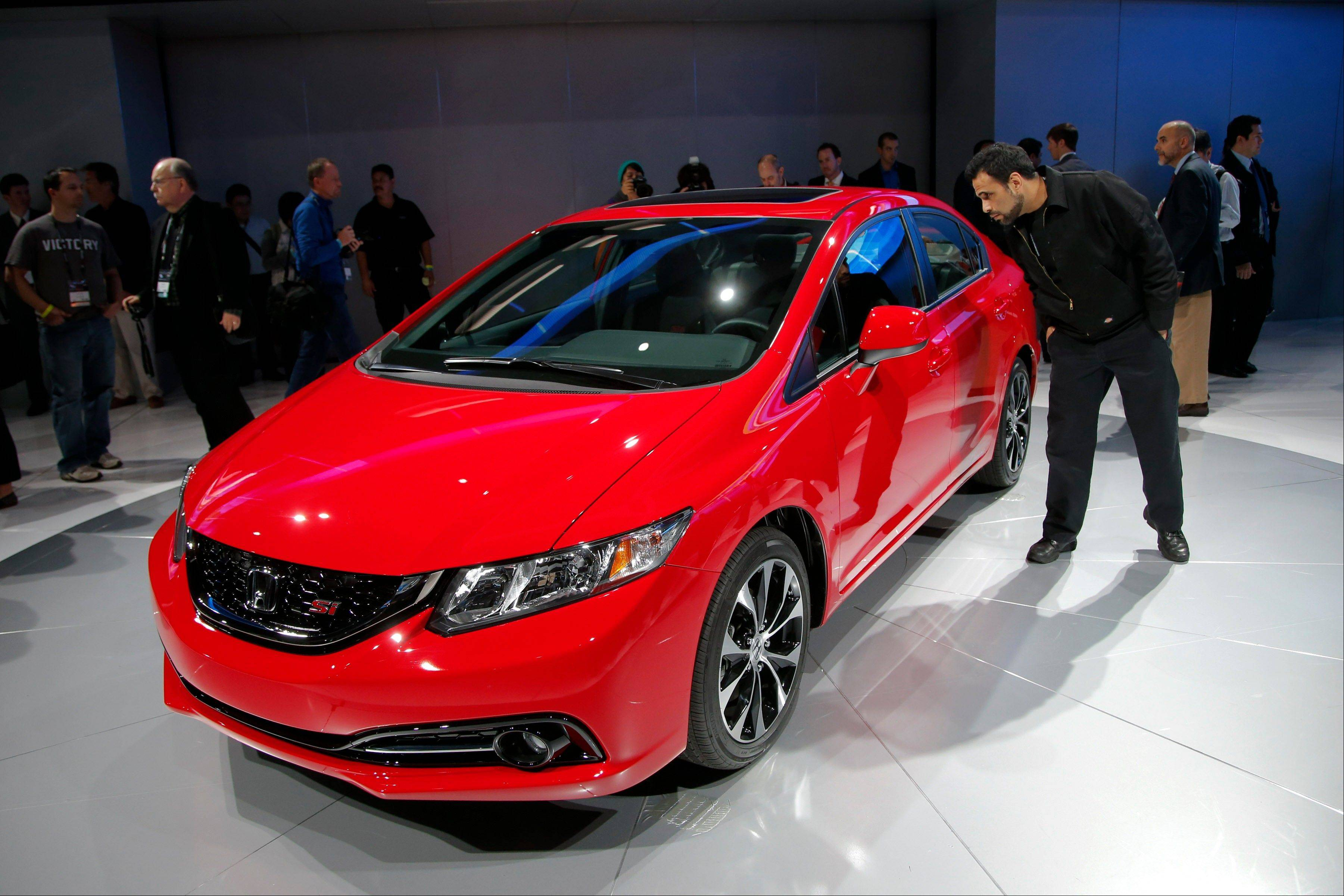 Show attendees look at the new Honda Civic at the LA Auto Show in Los Angeles Thursday.