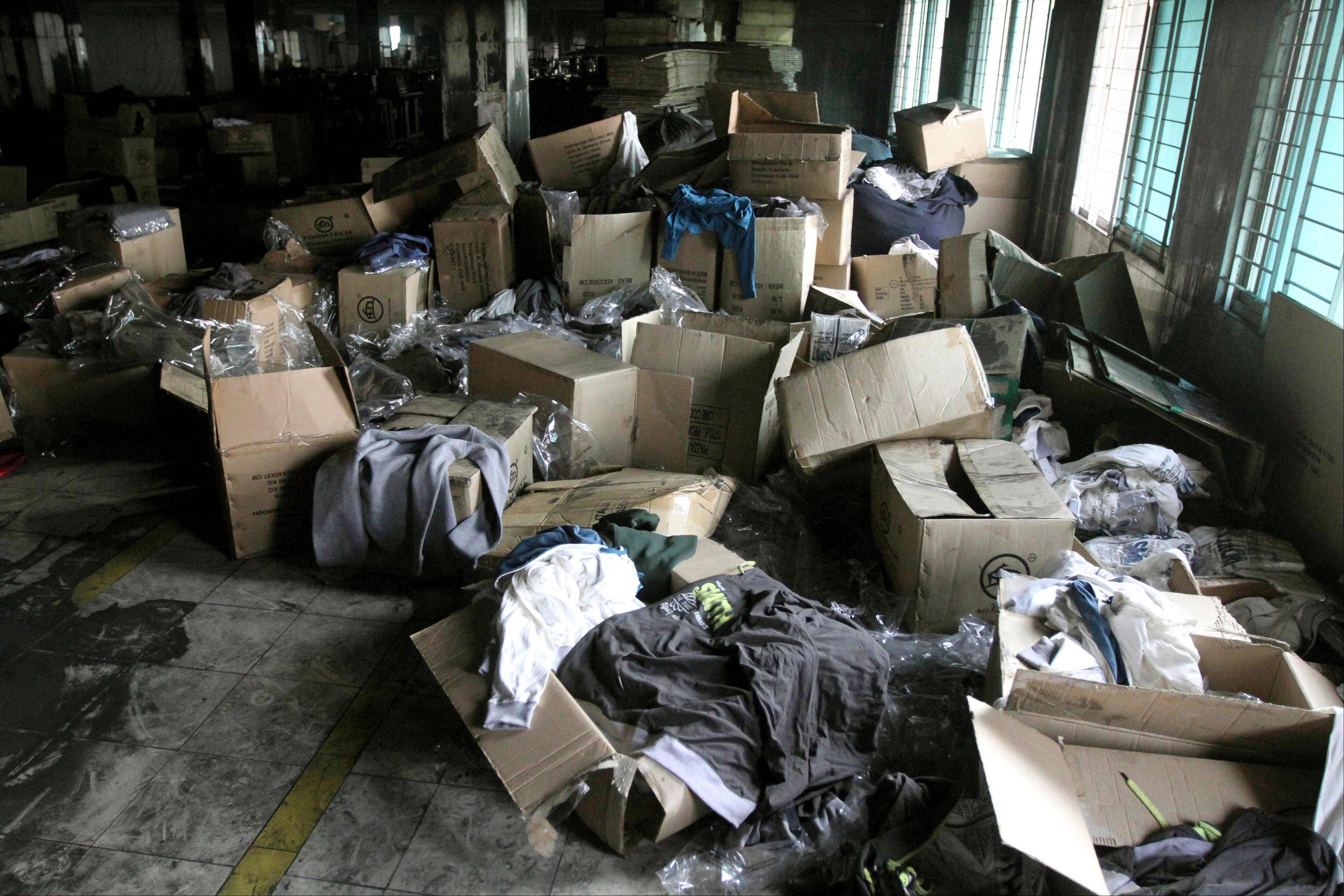 Boxes of garments lay near equipment charred in the fire that killed 112 workers Saturday at the Tazreen Fashions Ltd. factory,on the outskirts of Dhaha, Bangladesh, Wednesday.